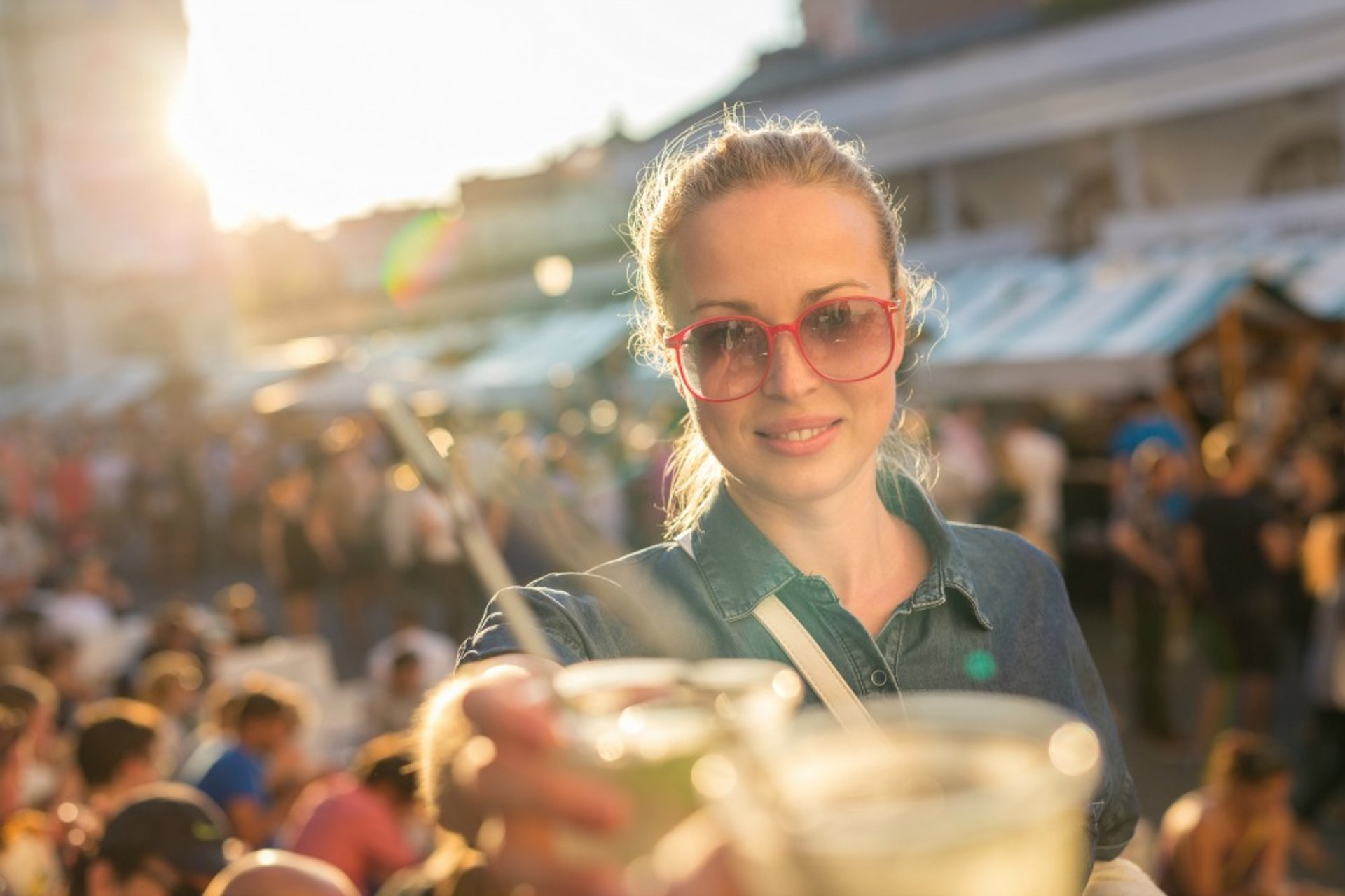 Woman at crowded venue reaching for cold drink.