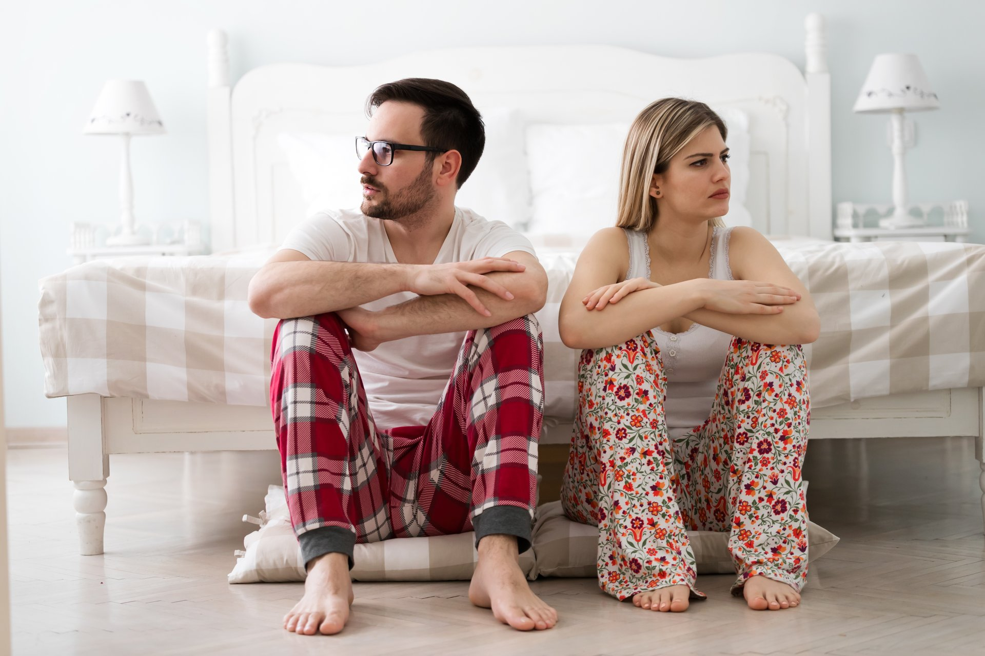 Couple in pajamas facing opposite directions.