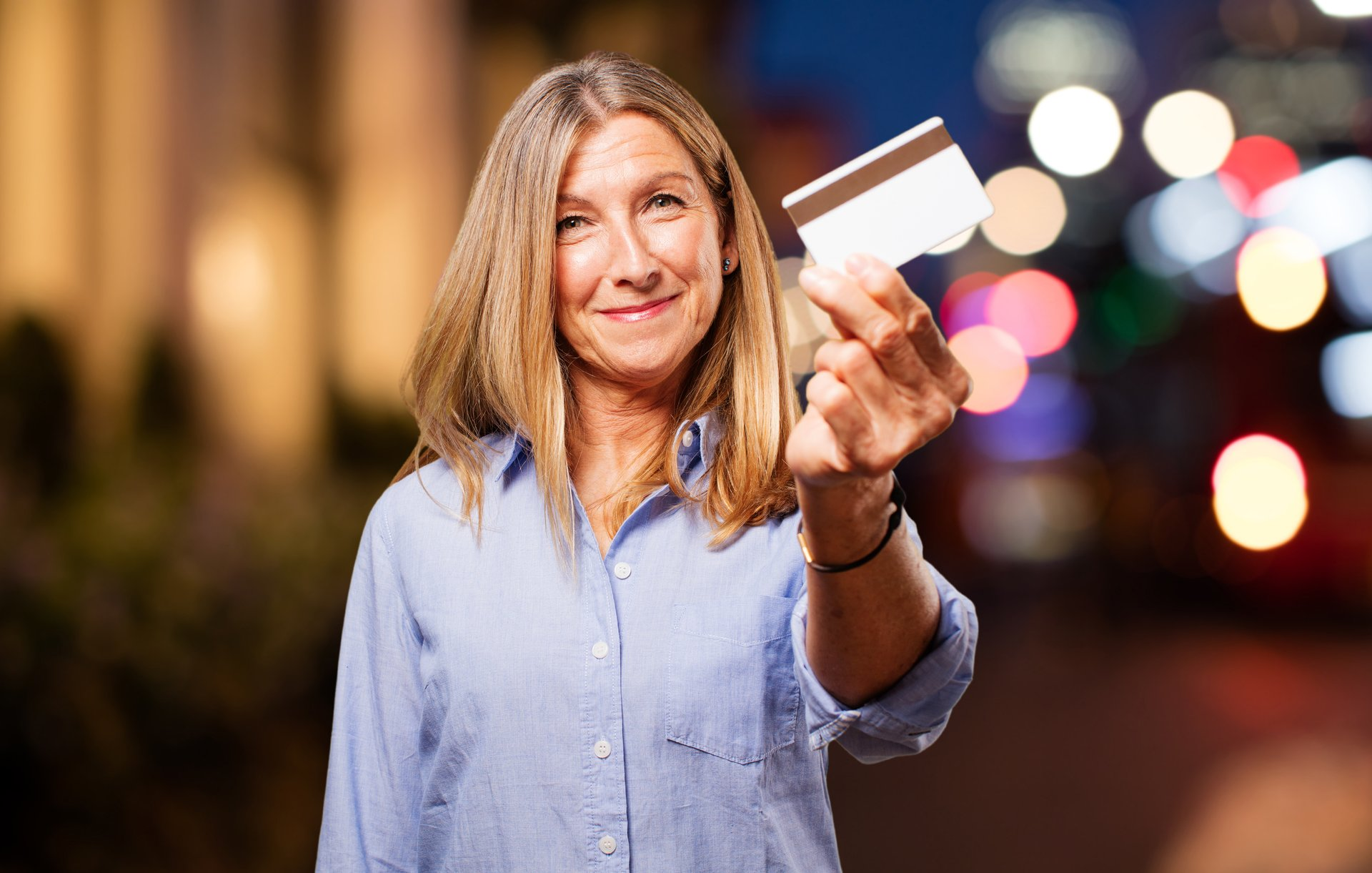A senior woman holds up a credit card
