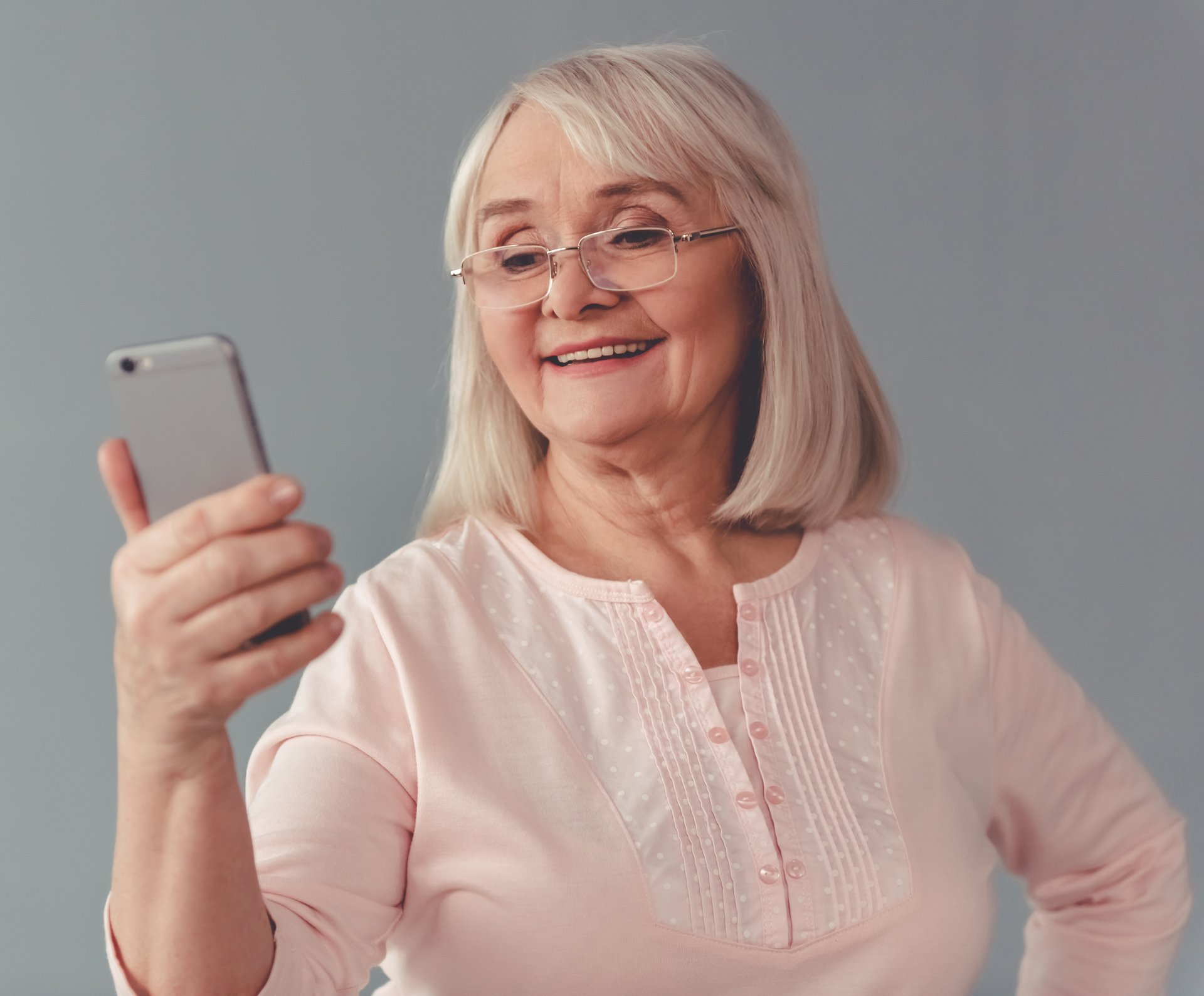 An older woman in glasses smiles while holding a smartphone