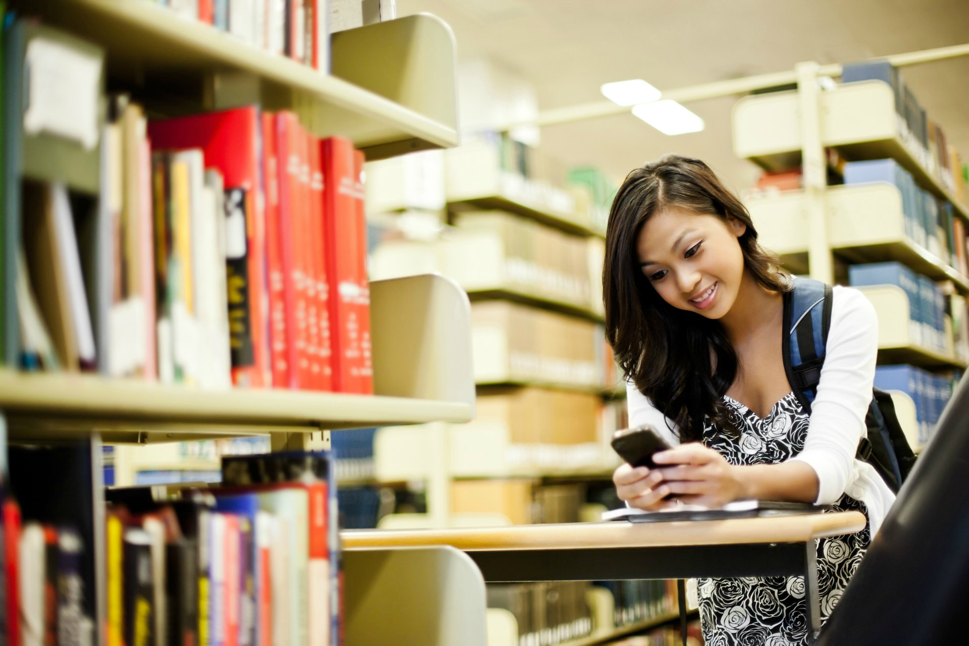 Woman student in library, looking at cellphone