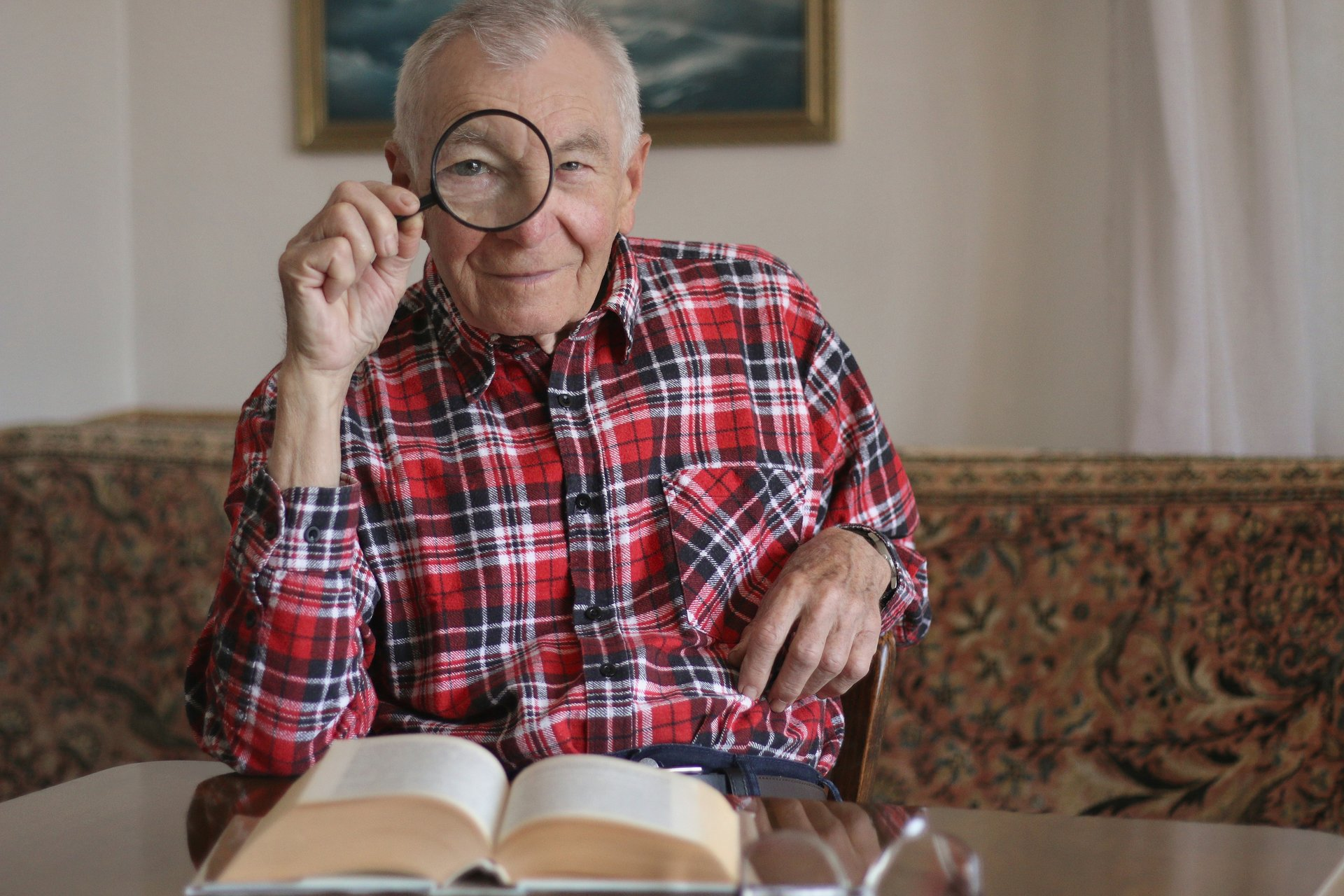 Older man looking through magnifying glass at camera