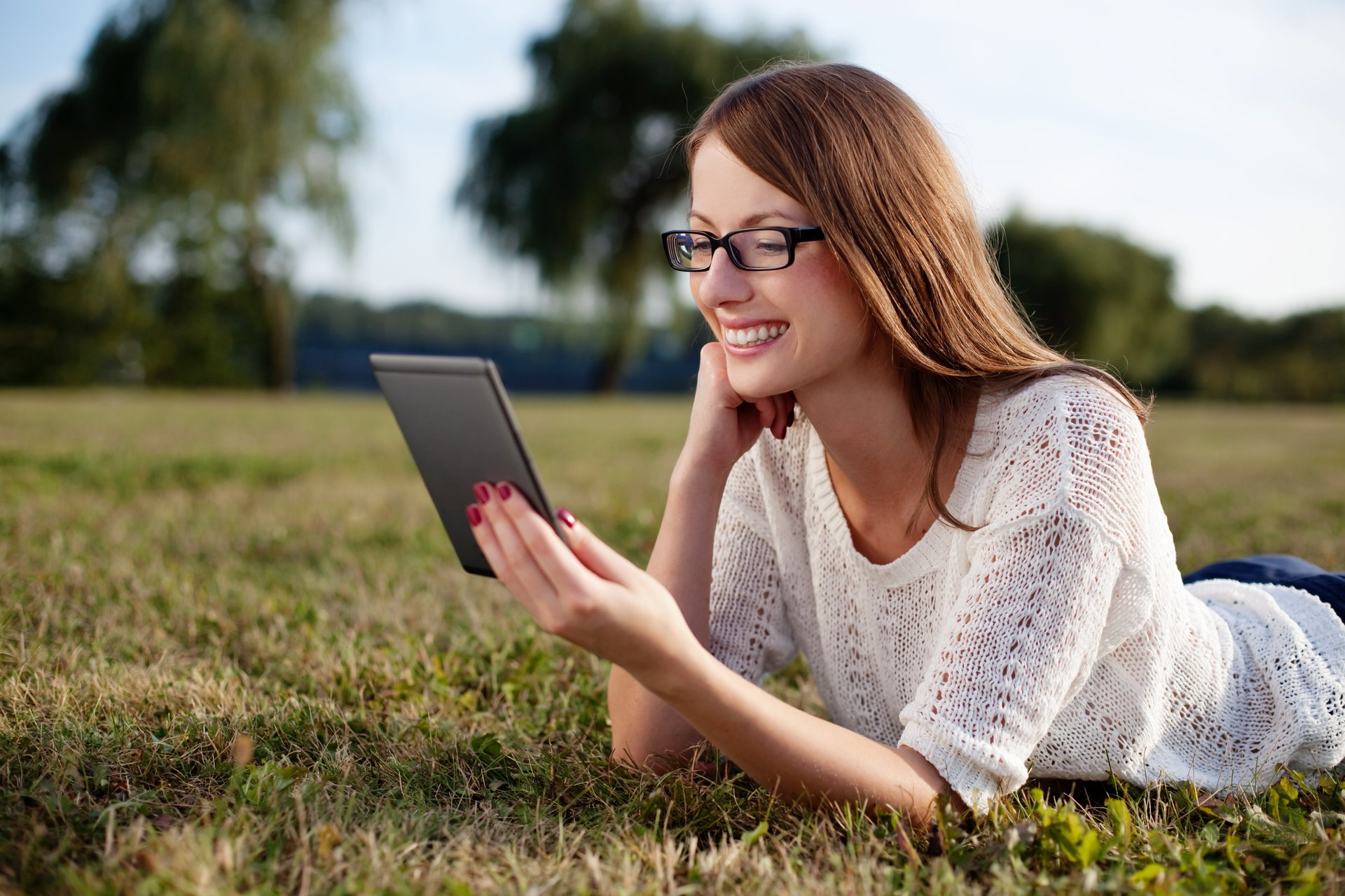 A woman smiles while enjoying reading an e-book on an e-reader and lying on the grass outside
