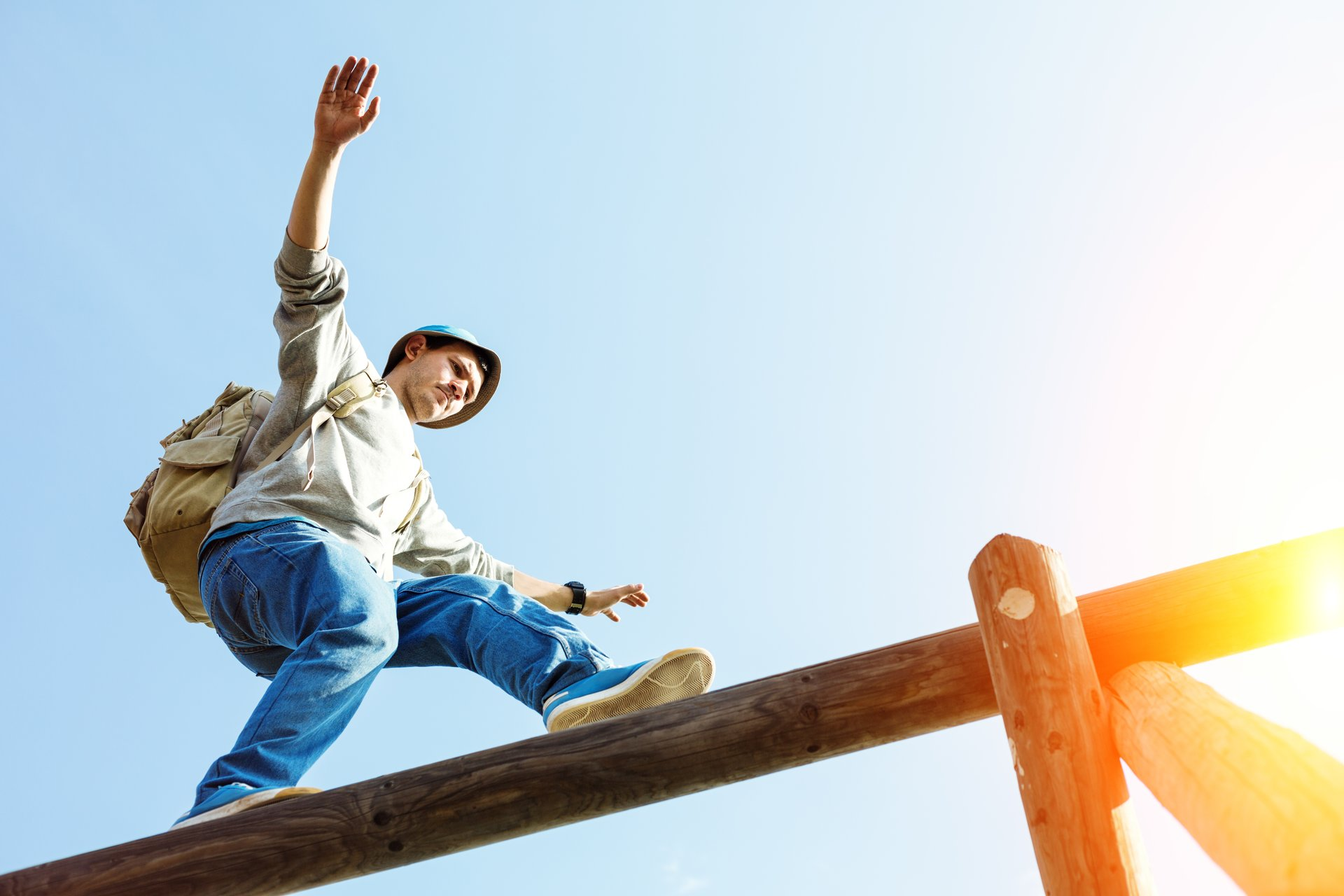 Young man balancing on a fence.