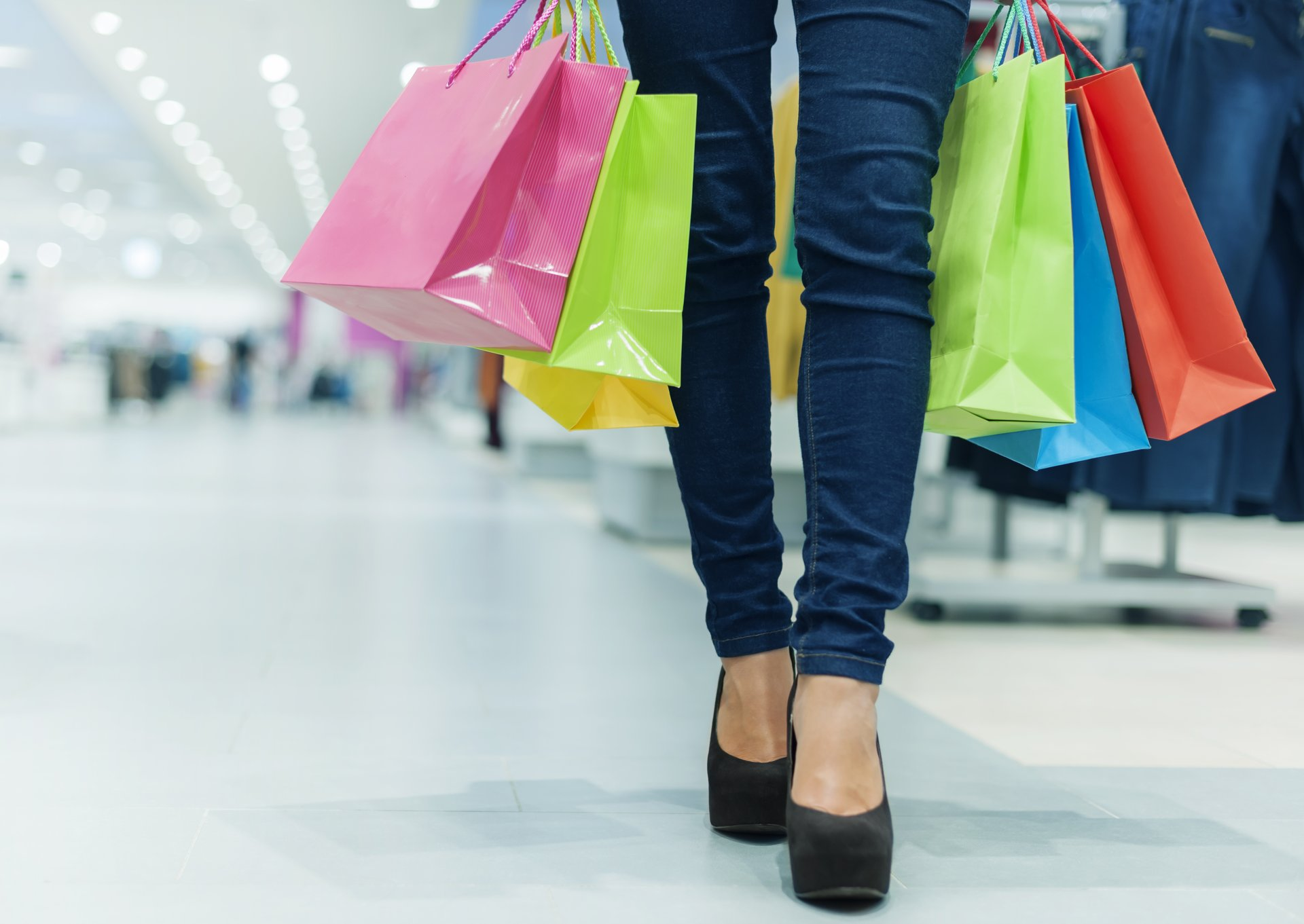 Woman's legs, hands with lots of shopping bags.