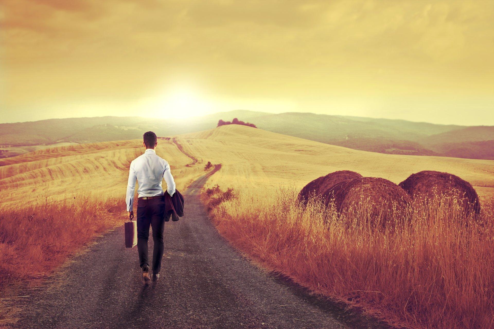 Man in suit walking on long road towards sun.