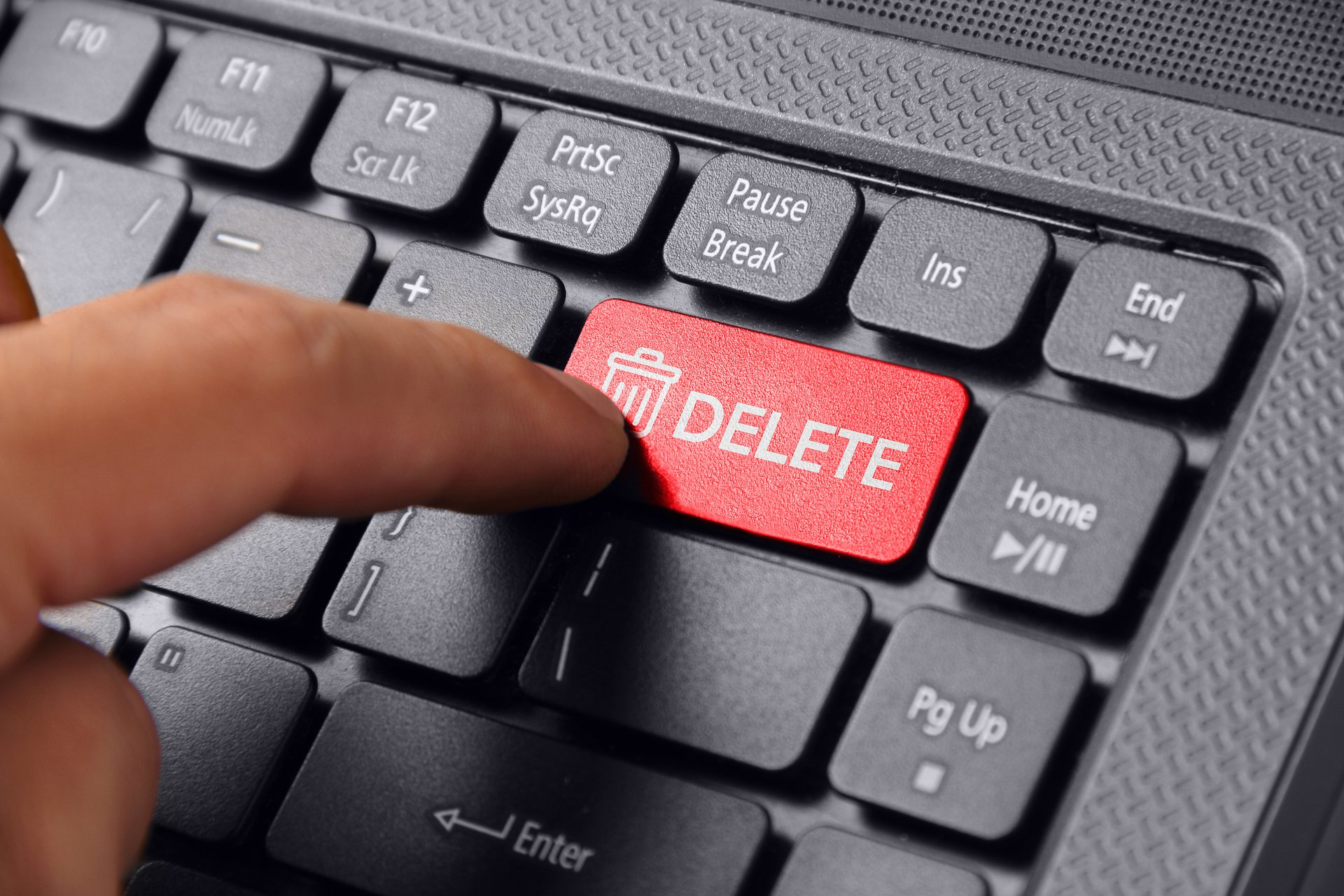 """Hand pressing """"delete"""" button on keyboard."""