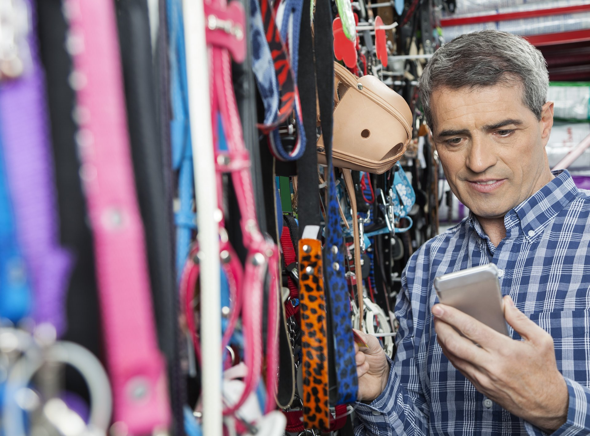 Man shopping, looking at cellphone