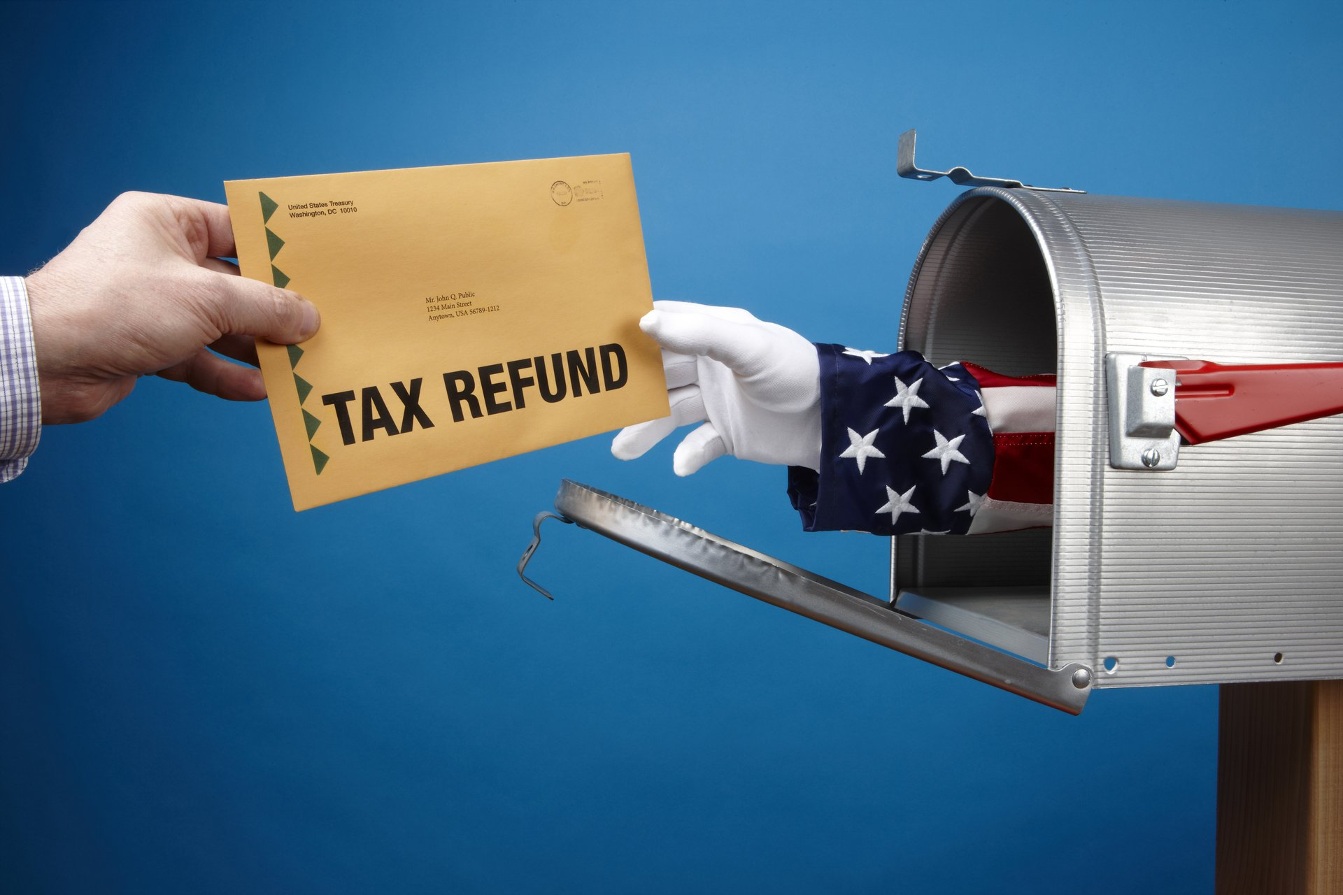 Tax refund check coming out of mailbox