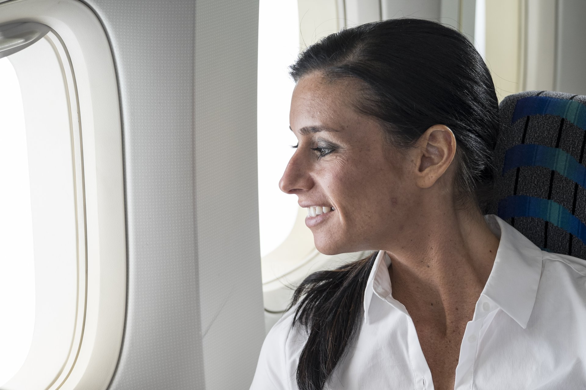 Woman looking out of an airplane window.