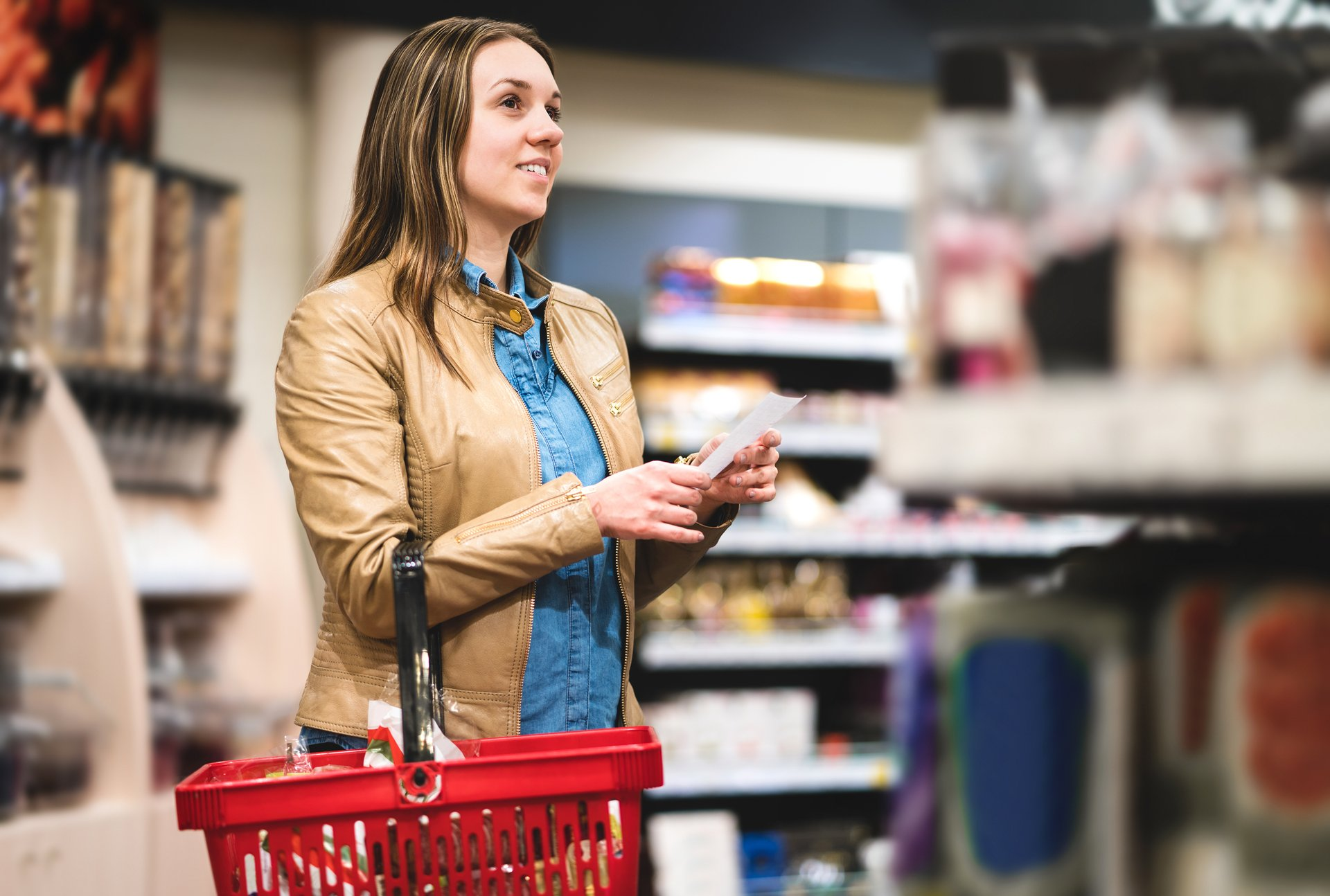 Woman with shopping list in grocery store.