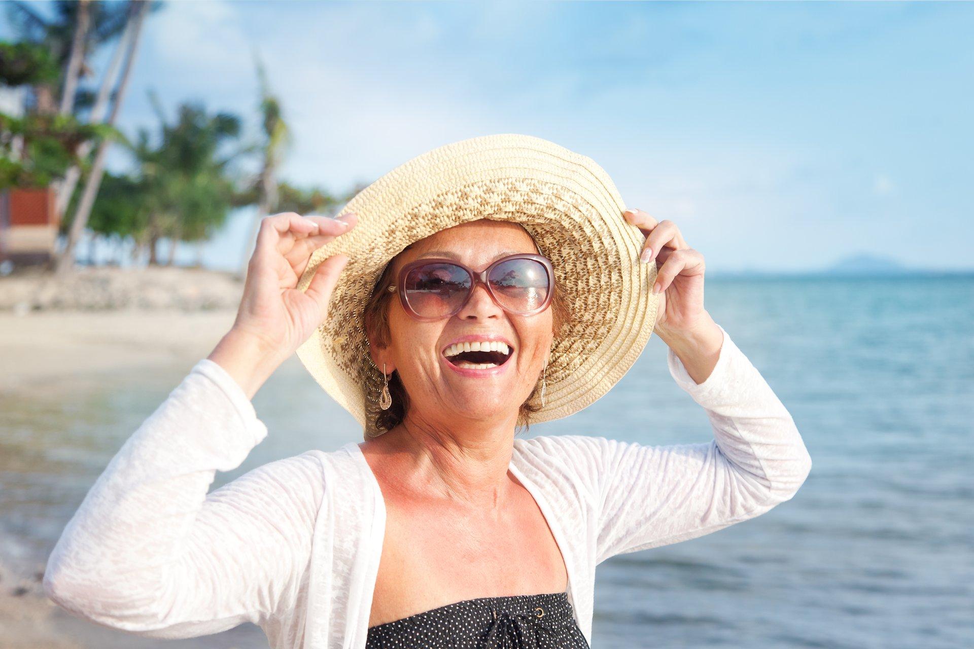Woman in sunhat on beach.