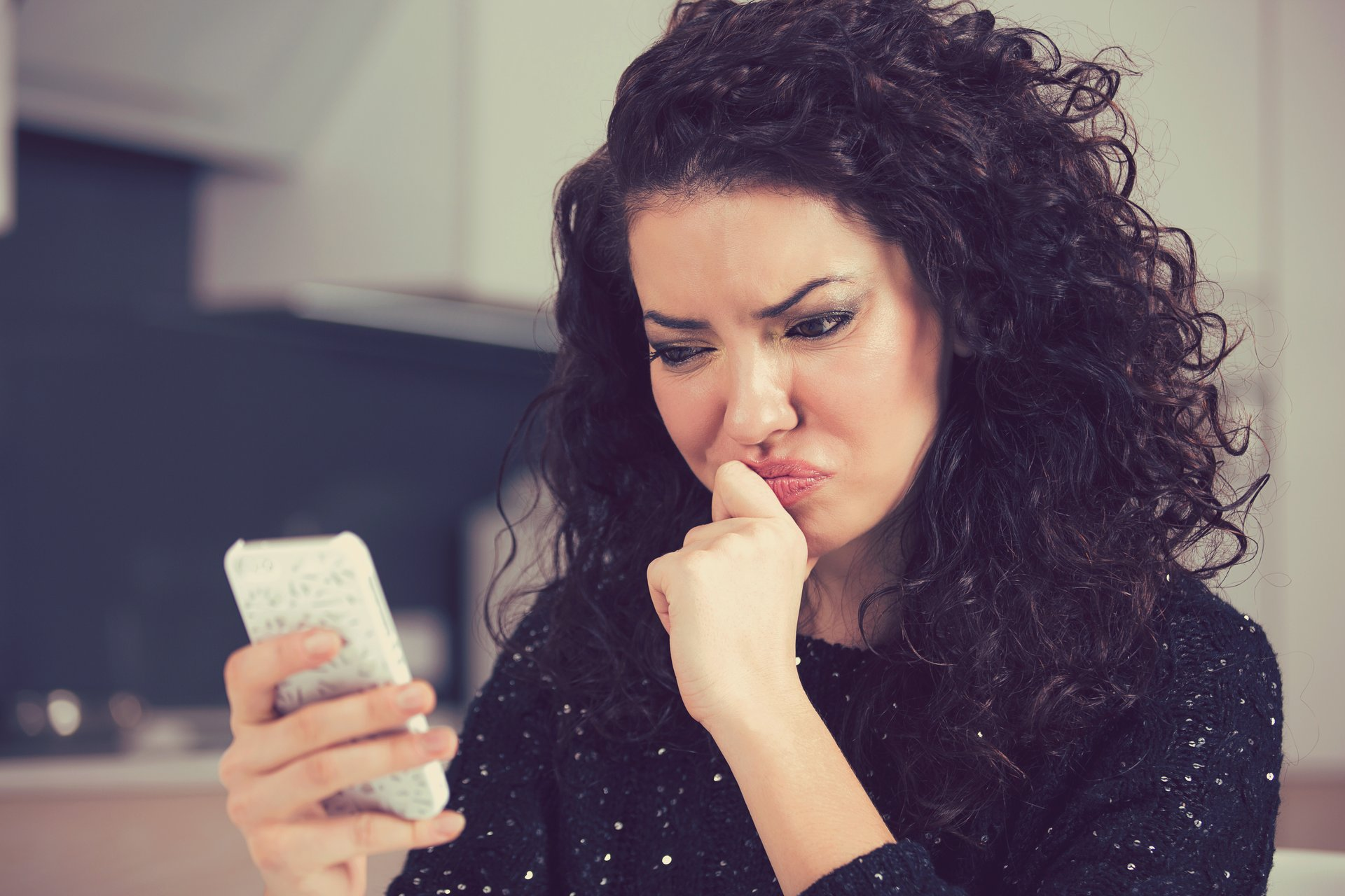 Woman looking stressed, looking at cellphone