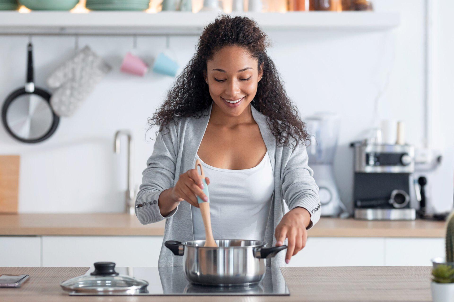 Happy woman preparing dinner at home
