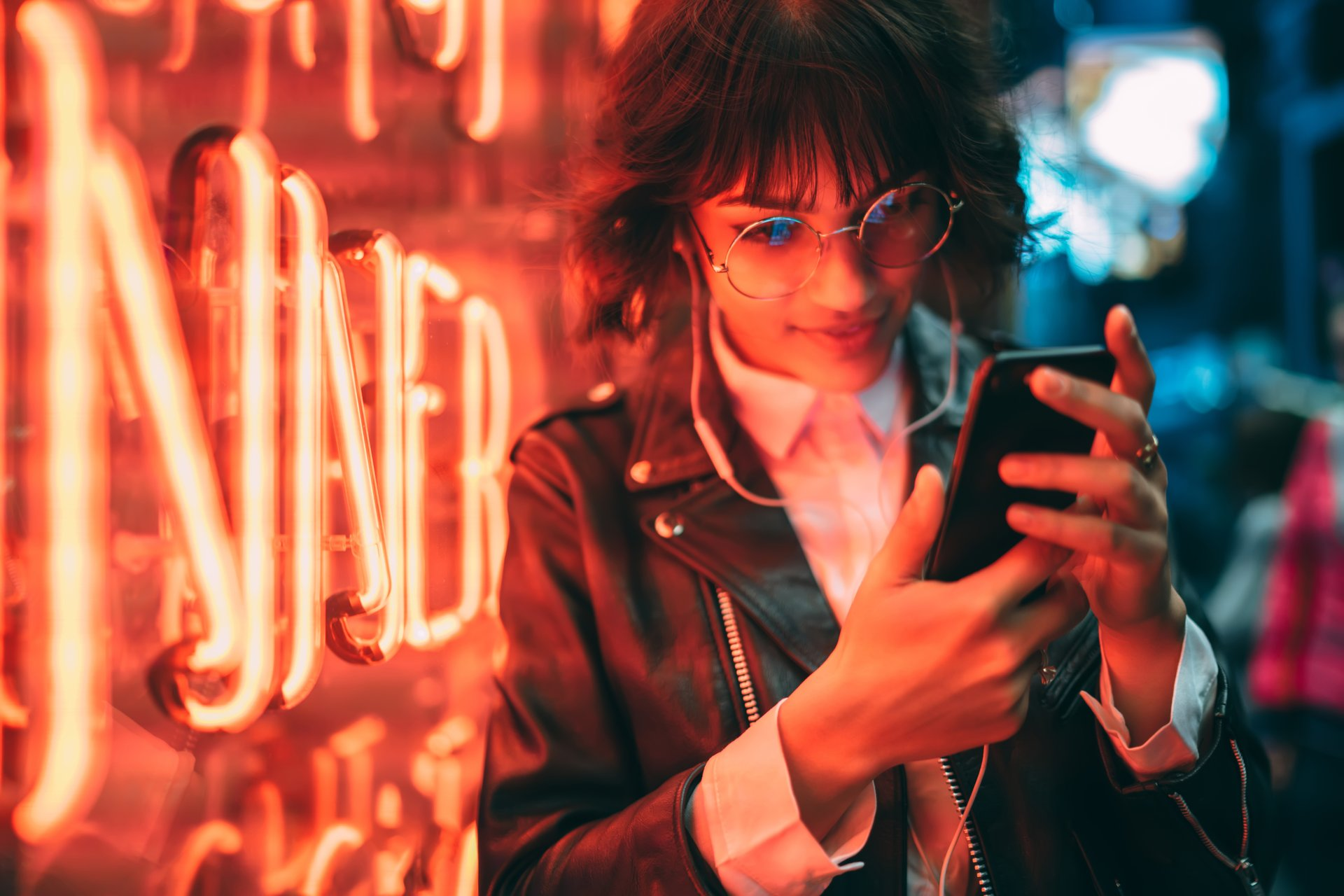 Person on cellphone near neon lights