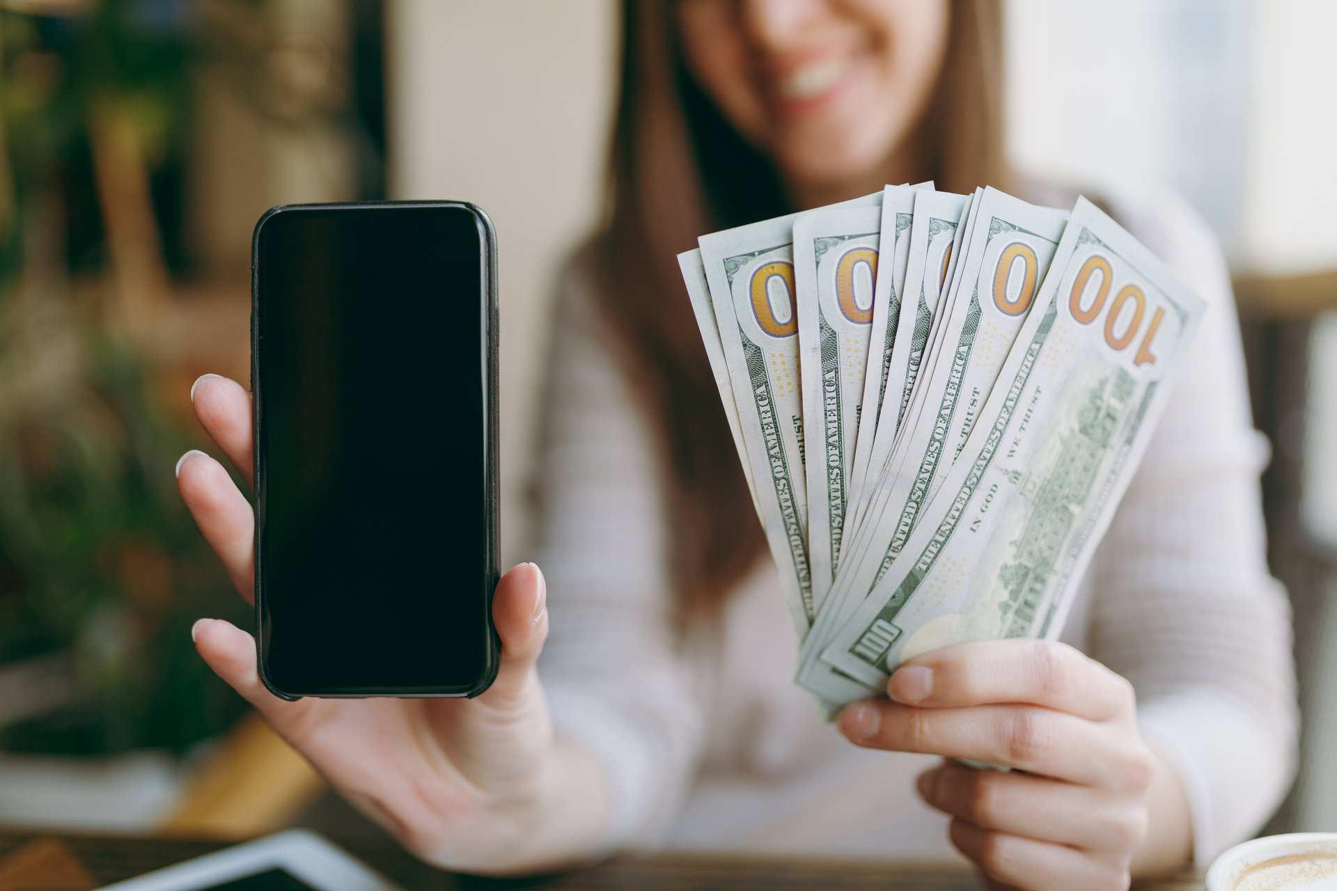 Woman holding a cellphone and cash