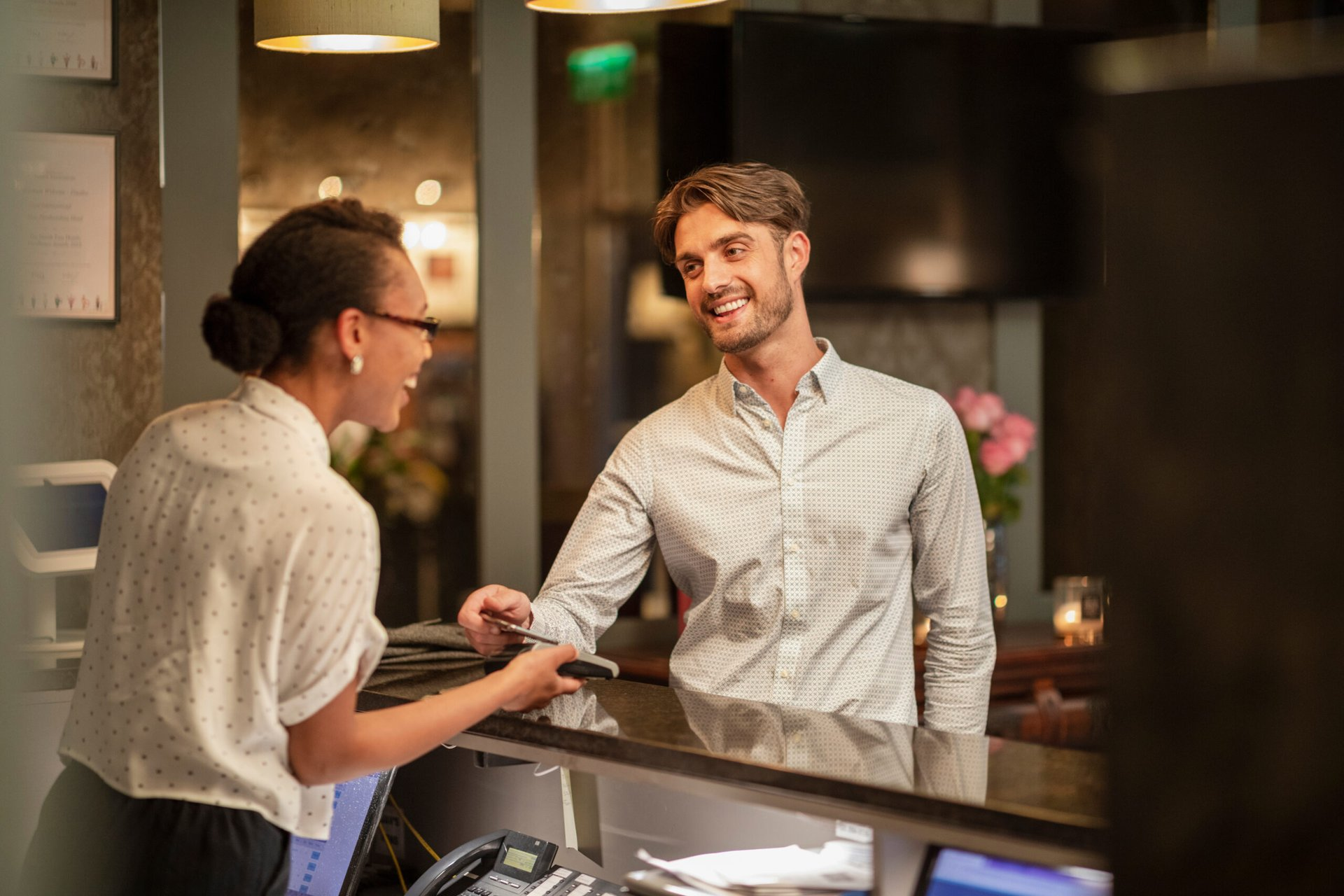 Man checking into hotel with credit card rewards