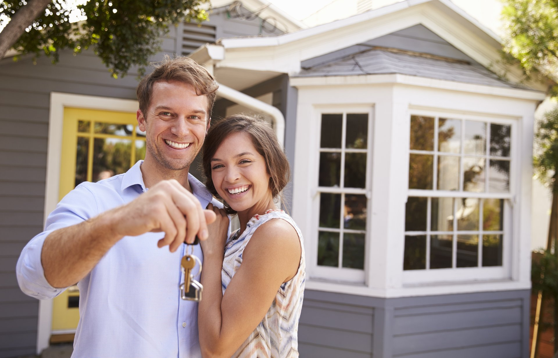 Couple standing in front of a home