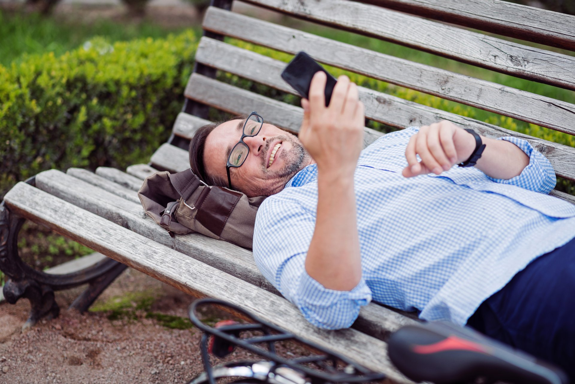 Man with cellphone on park bench