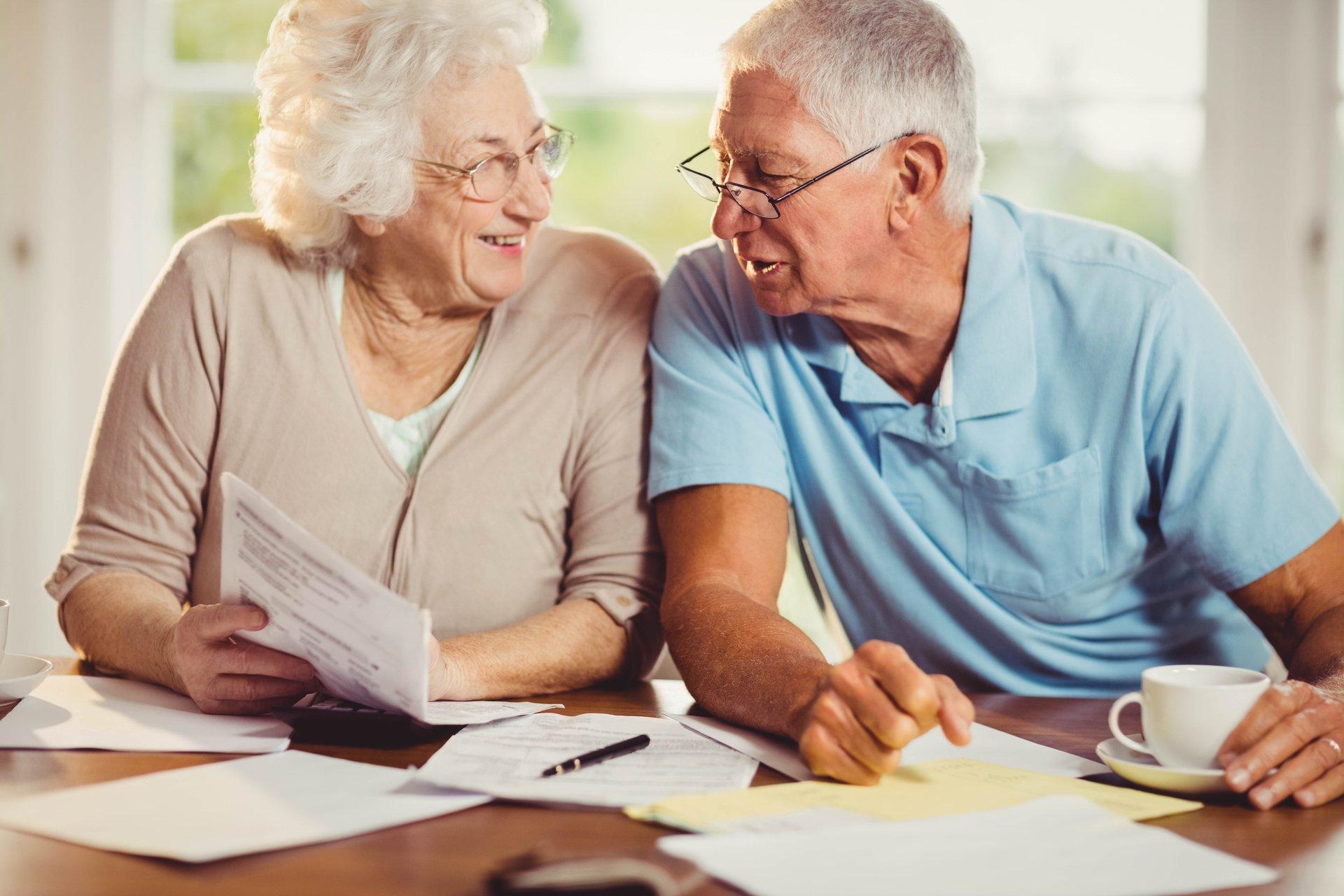 A senior couple pays bills