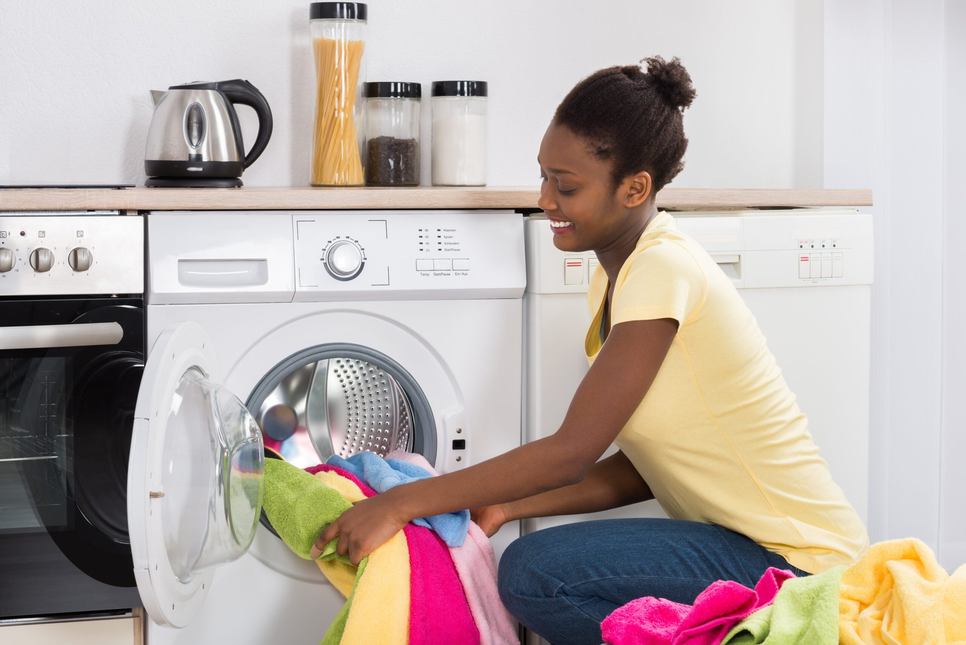 Woman putting laundry in a washing machine