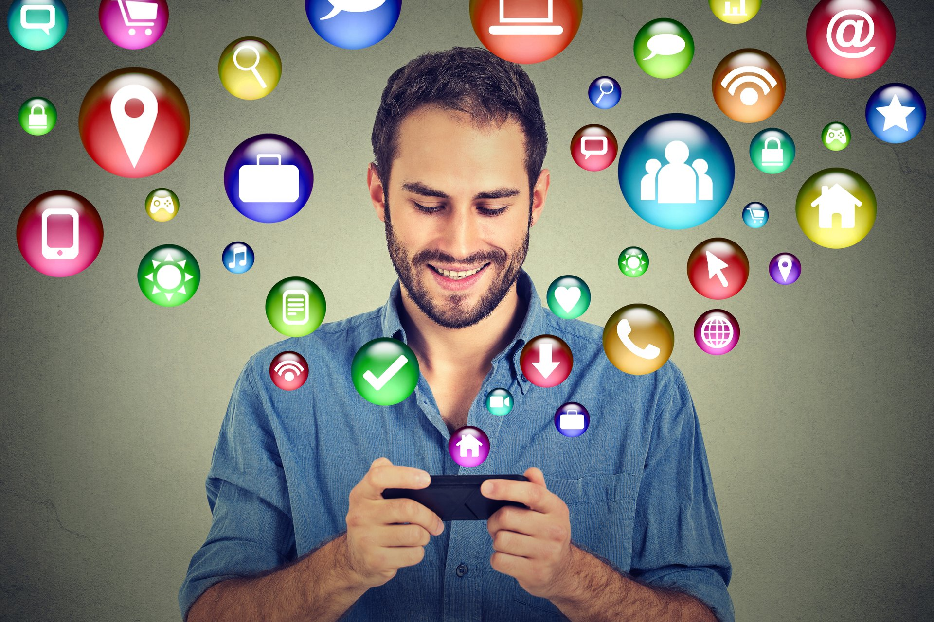 Man looking at cellphone with icons flying out.