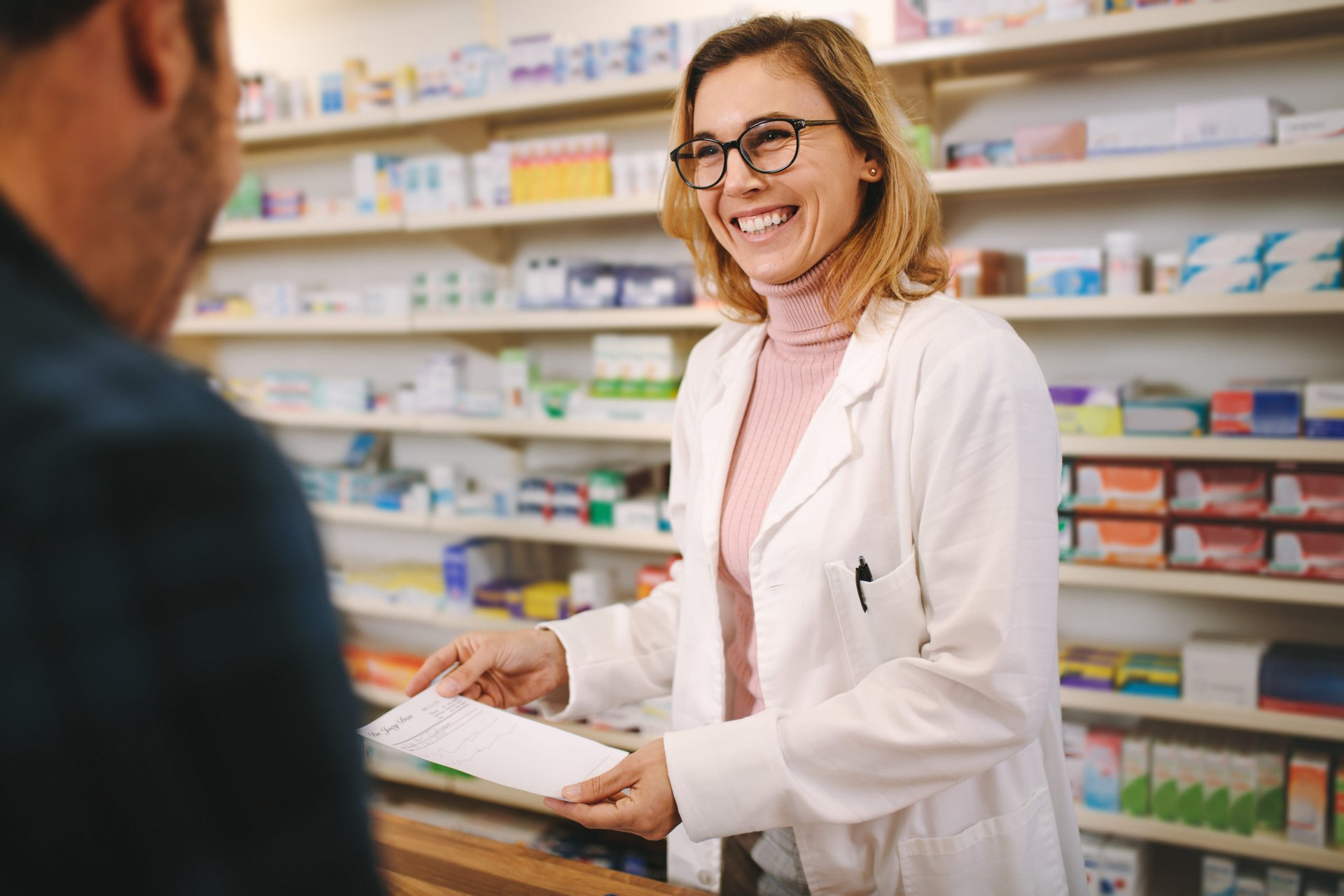 Pharmacist taking a prescription from a customer