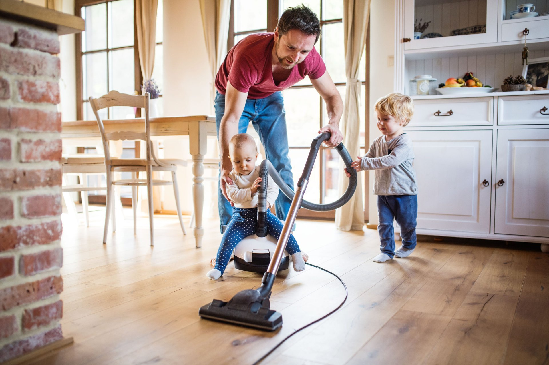 a man vacuums his kitchen