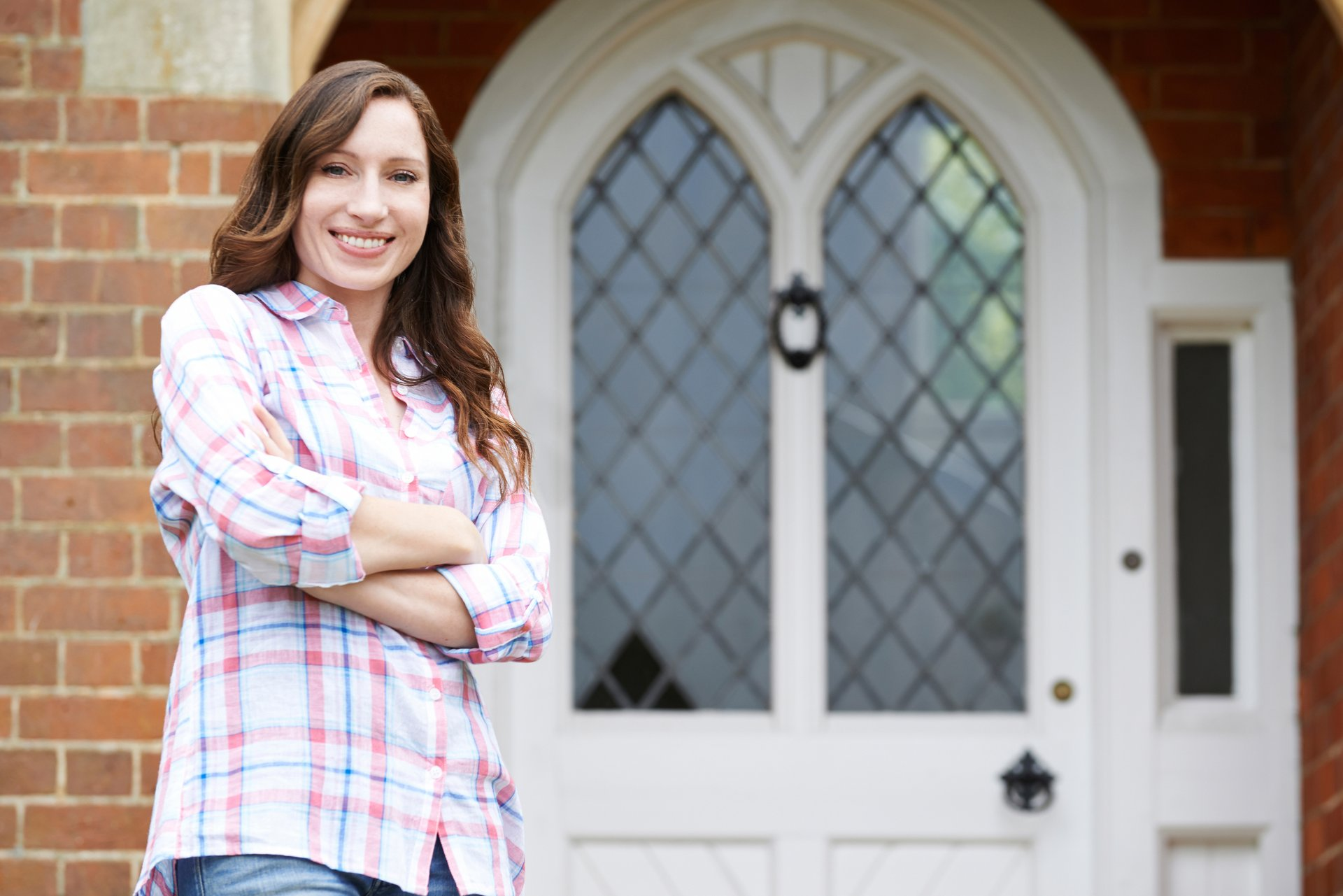 A woman stands outside the front door of her home