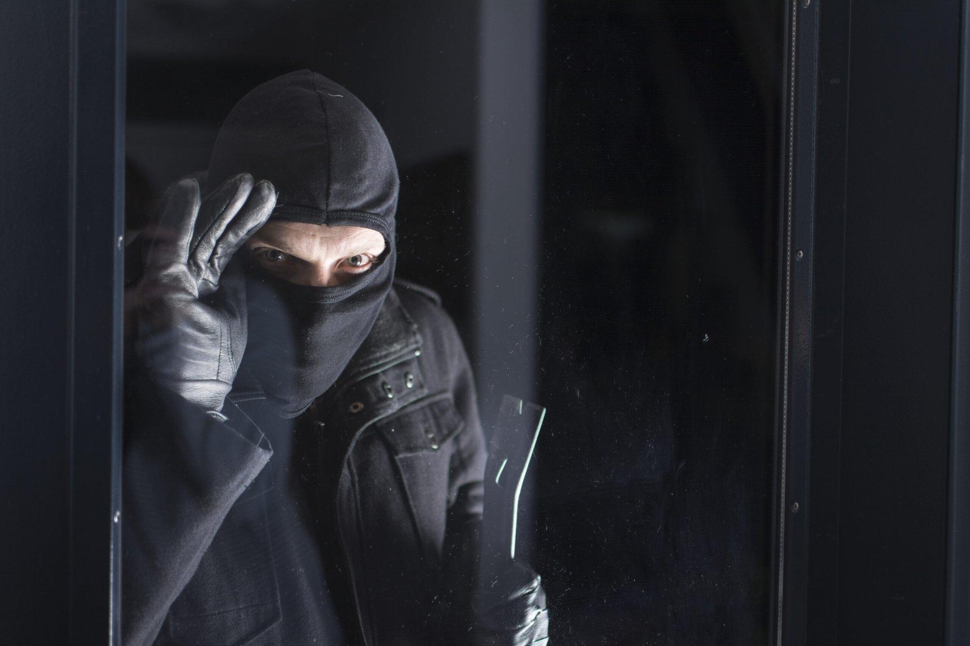 Burglar peering into a home