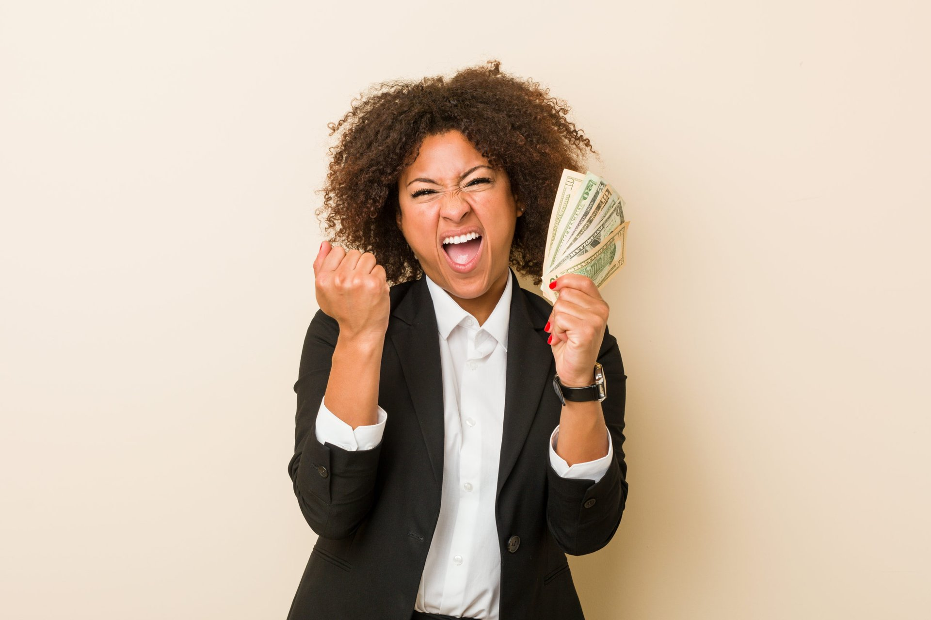 Excited businesswoman with cash