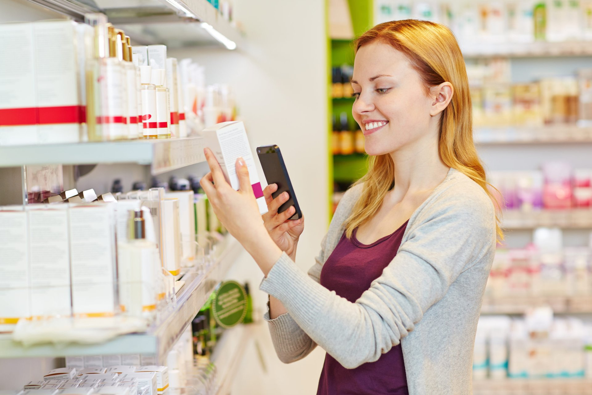 drugstore shopper comparing prices on her phone