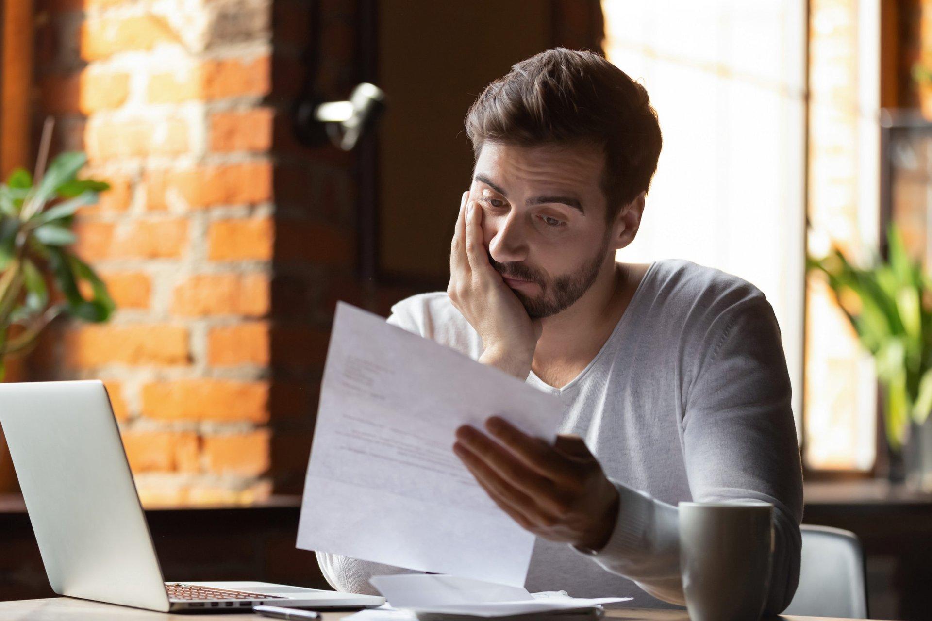 sad man reading his credit report