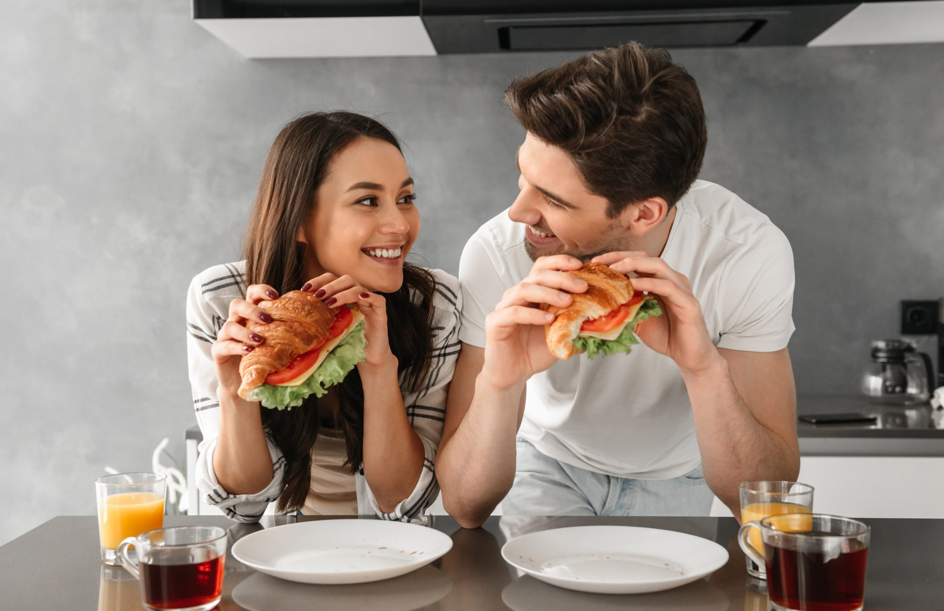 Couple eating sandwiches at home