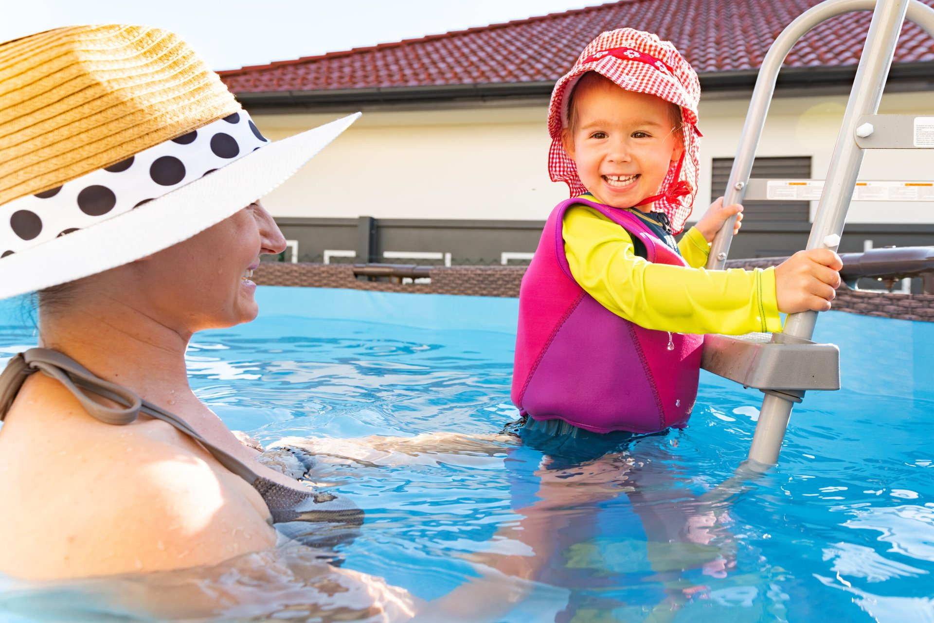 Mother and child in backyard pool