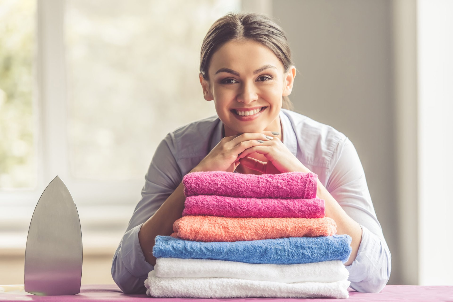 Happy woman with folded laundry