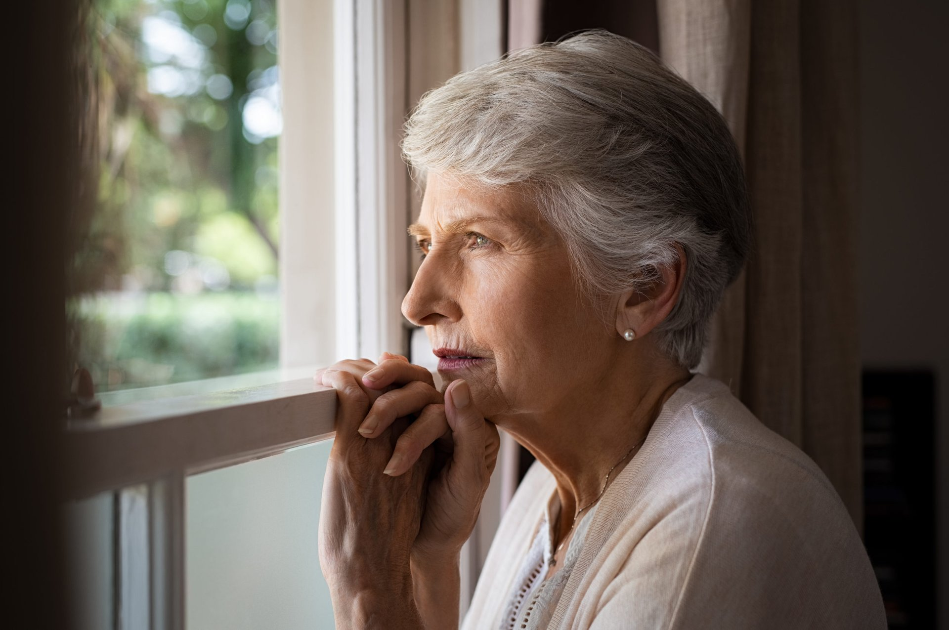 Worried senior looking out a window