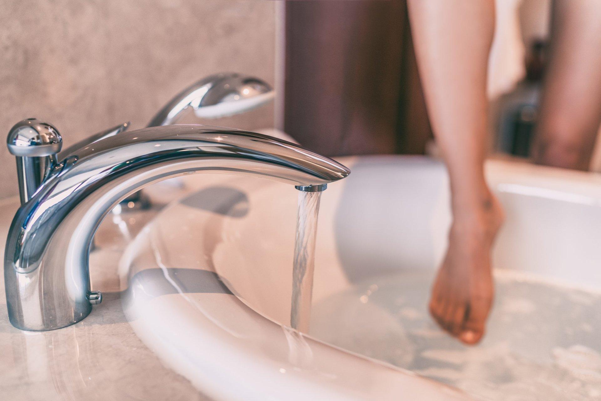 Woman stepping into a bathtub