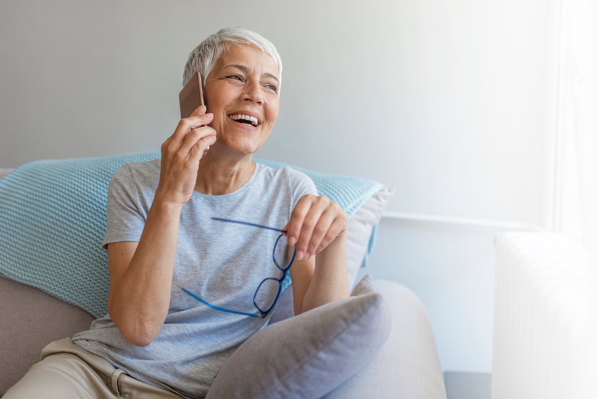 Senior woman talking on her mobile phone. Senior woman has a happy conversation at cellphone. Smiling senior woman using phone sitting on couch at home. - Image