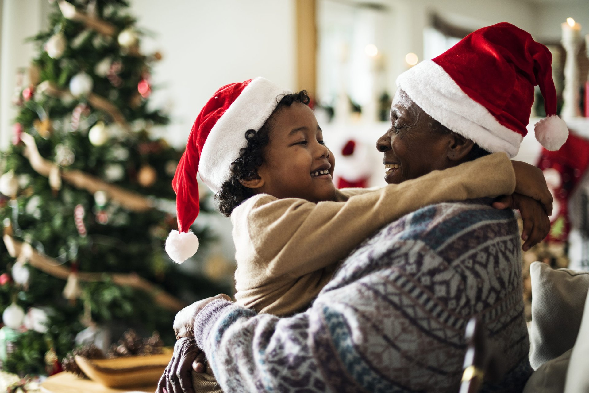 A parent and child in Santa hats hug in front of a Christmas tree