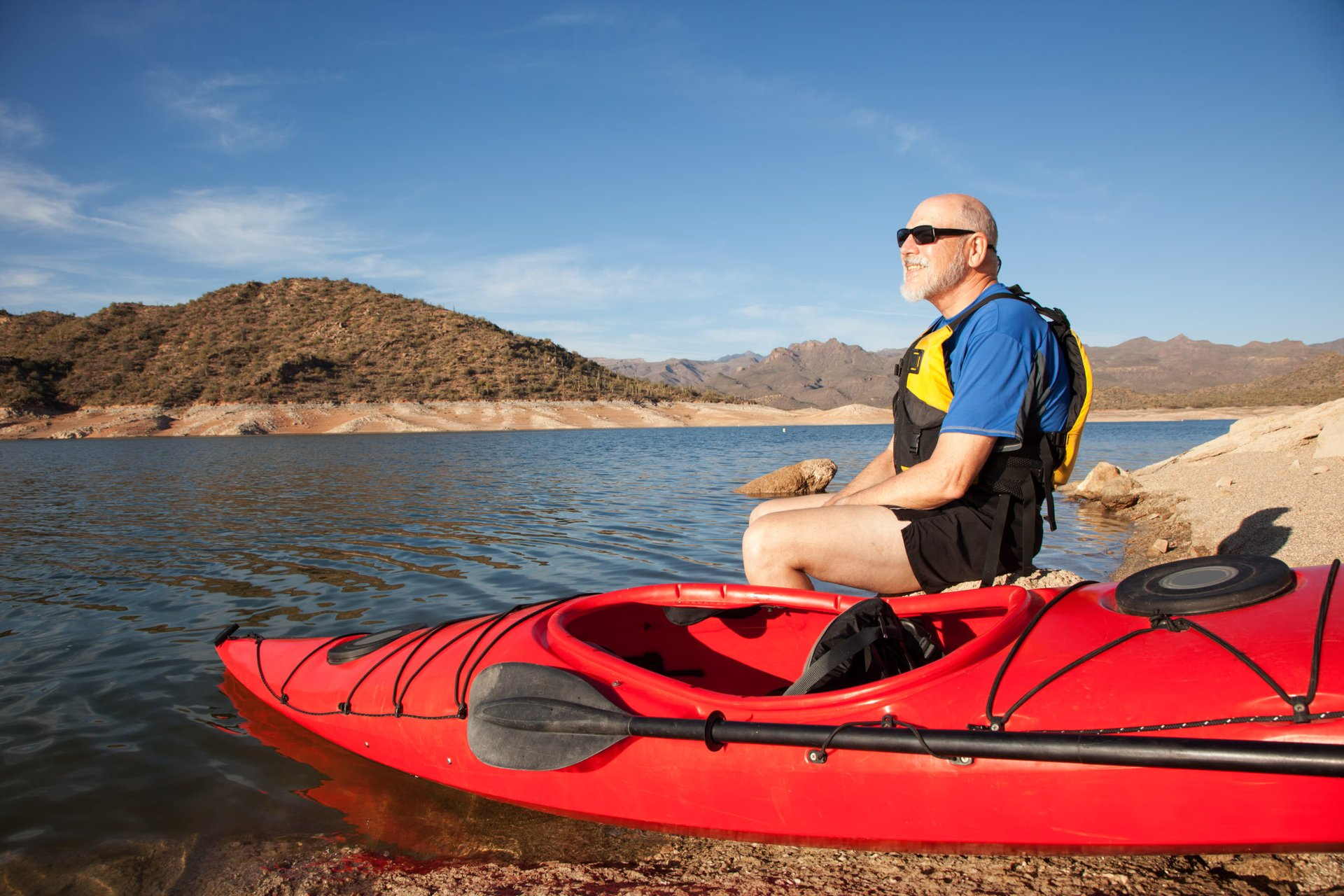 A senior takes a break on the shore of Bartlett Lake in Arizona during a kayak ride