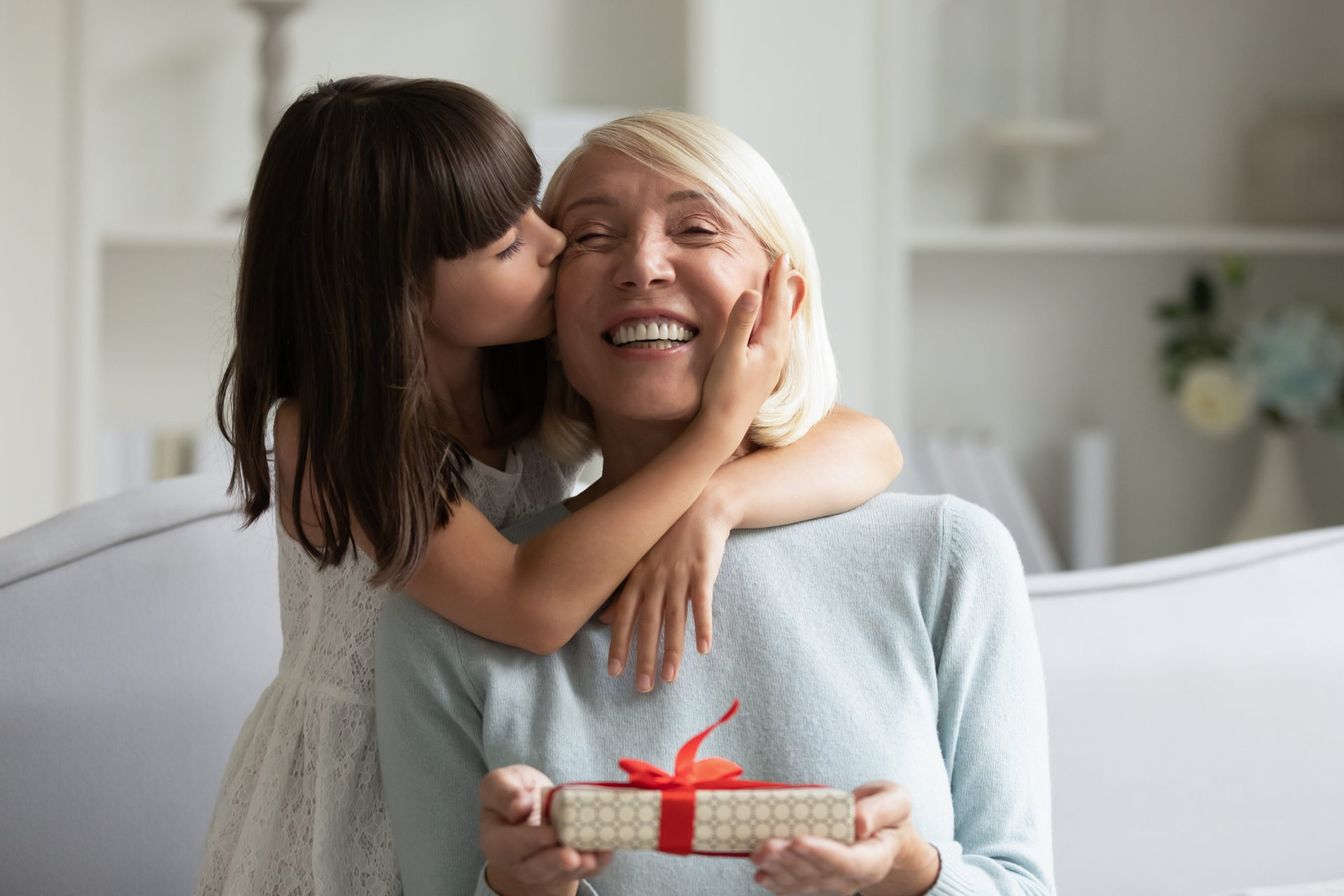 Child giving a gift to her grandmother