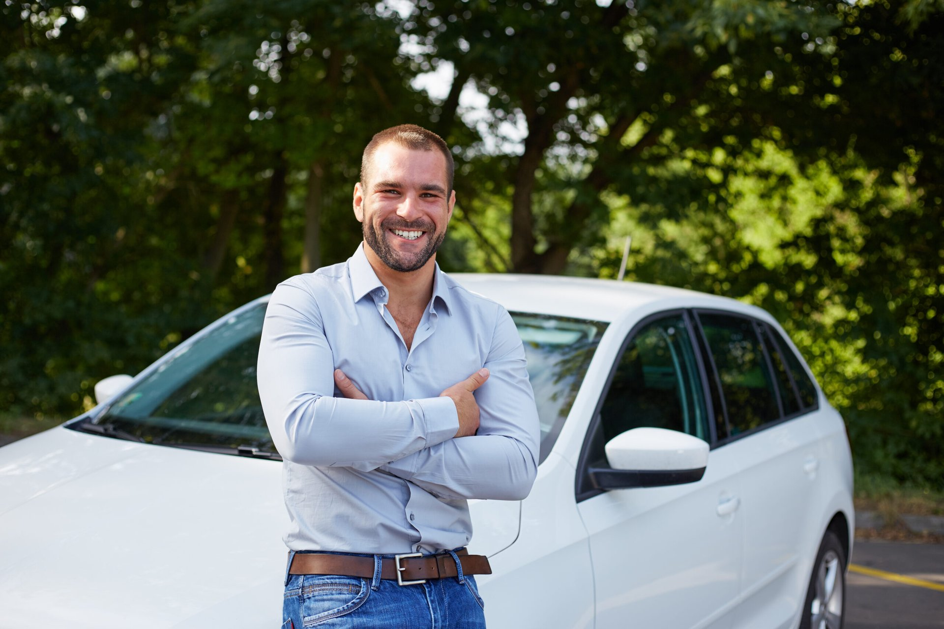 Happy man in front of a car