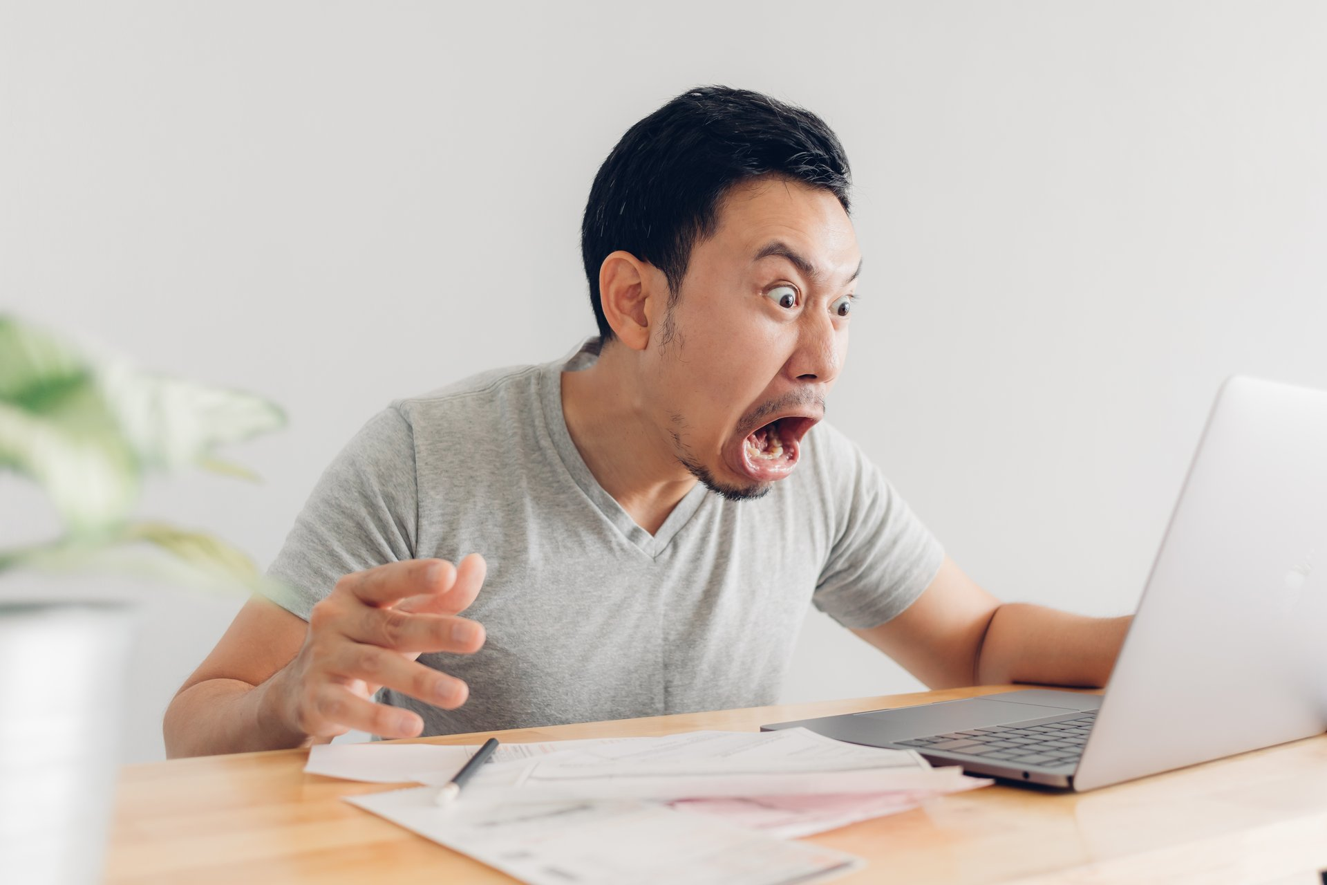 A young Asian man at his laptop computer is surprised and shocked by a bill