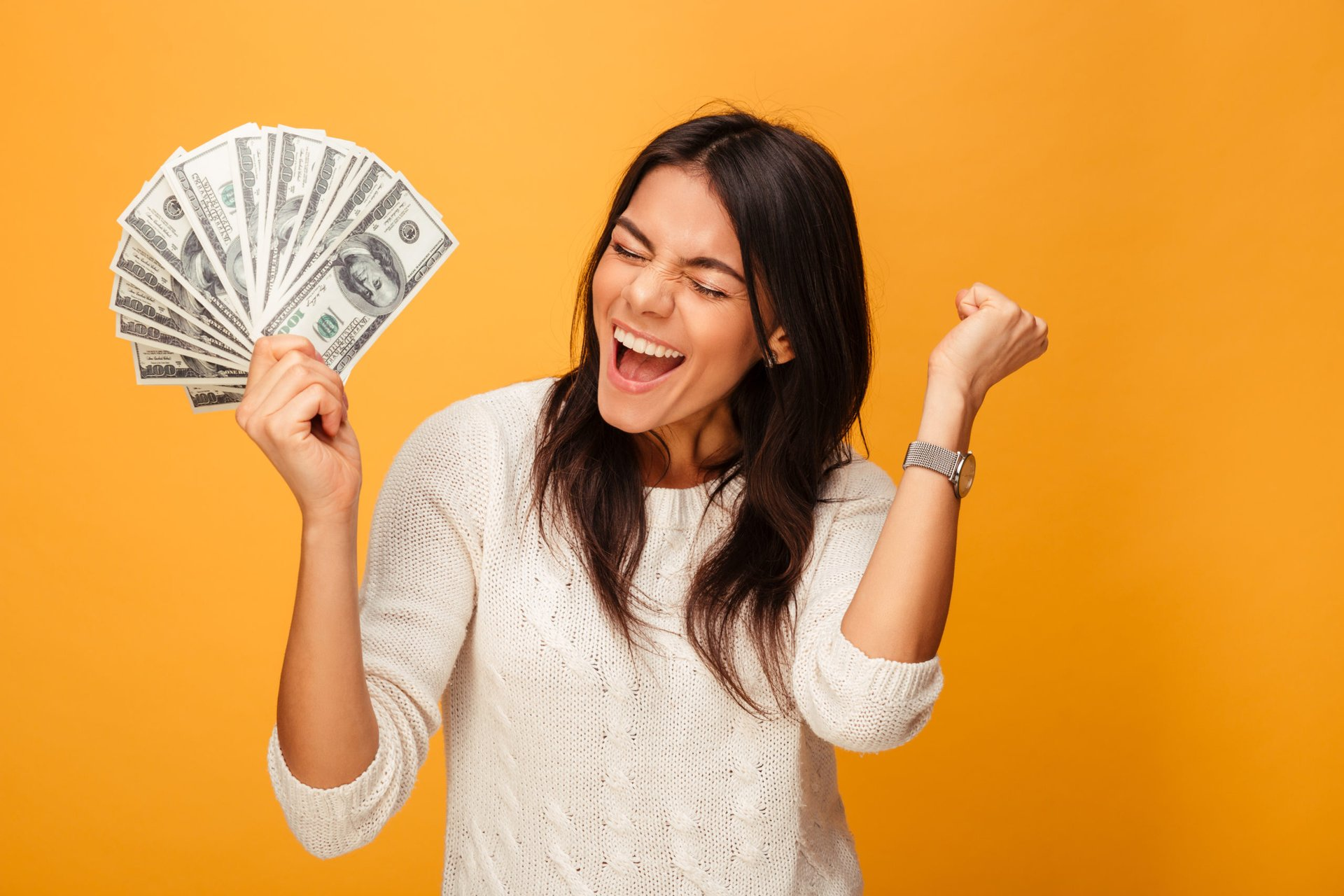 Happy woman holding hundred dollar bills