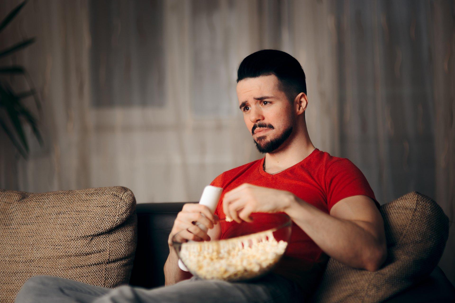 Sad man watching TV