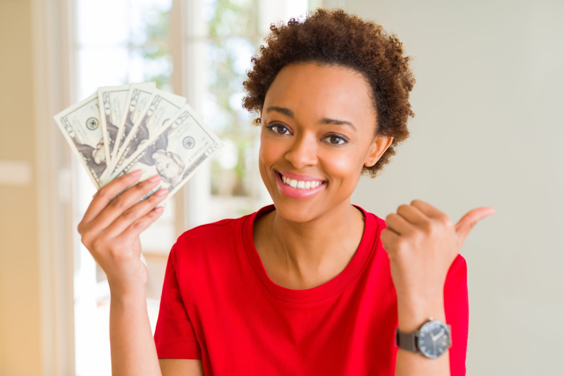 A young woman smiles while holding a fan of cash and giving the thumbs-up gesture