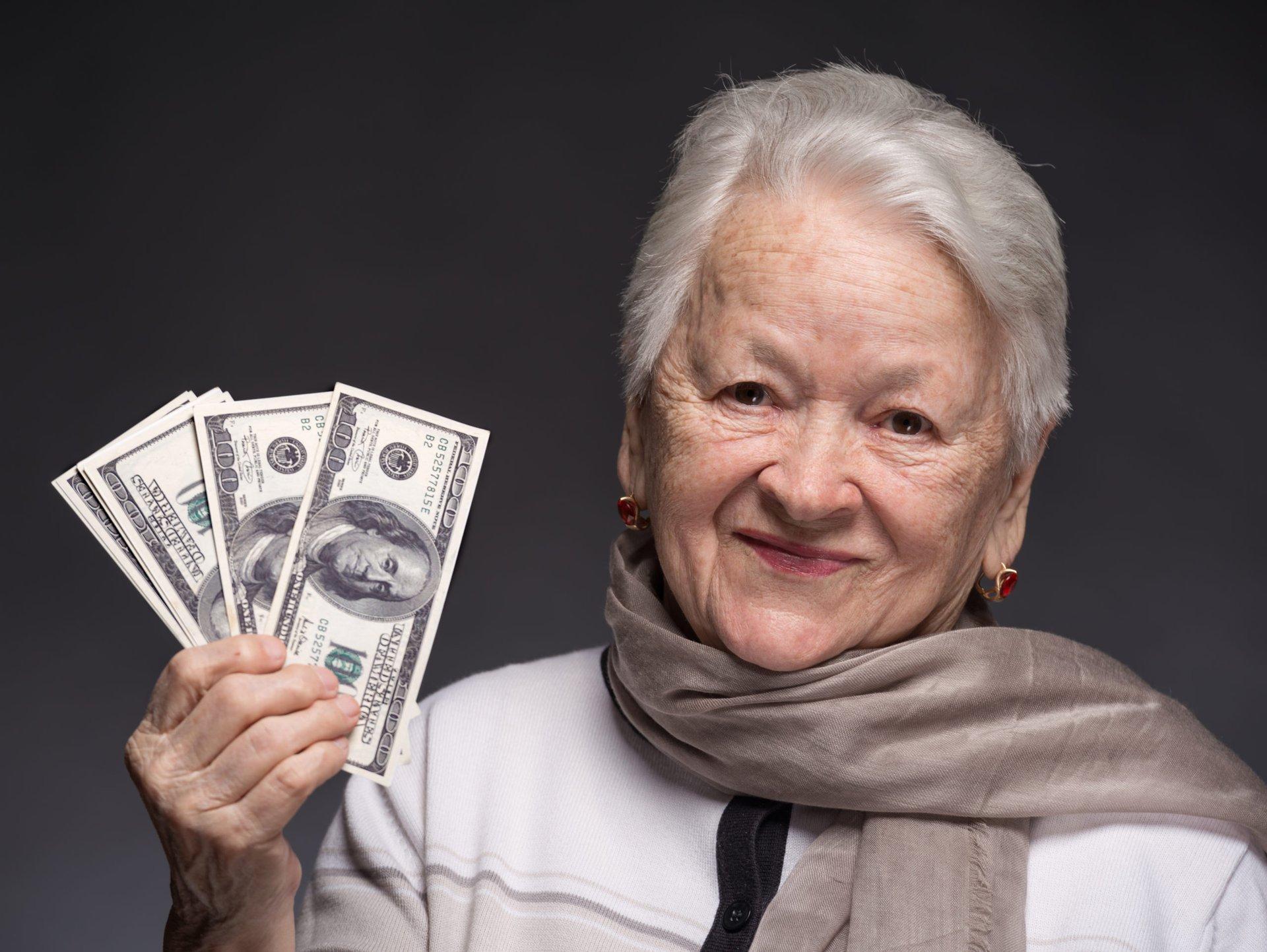 Smiling senior woman holding money