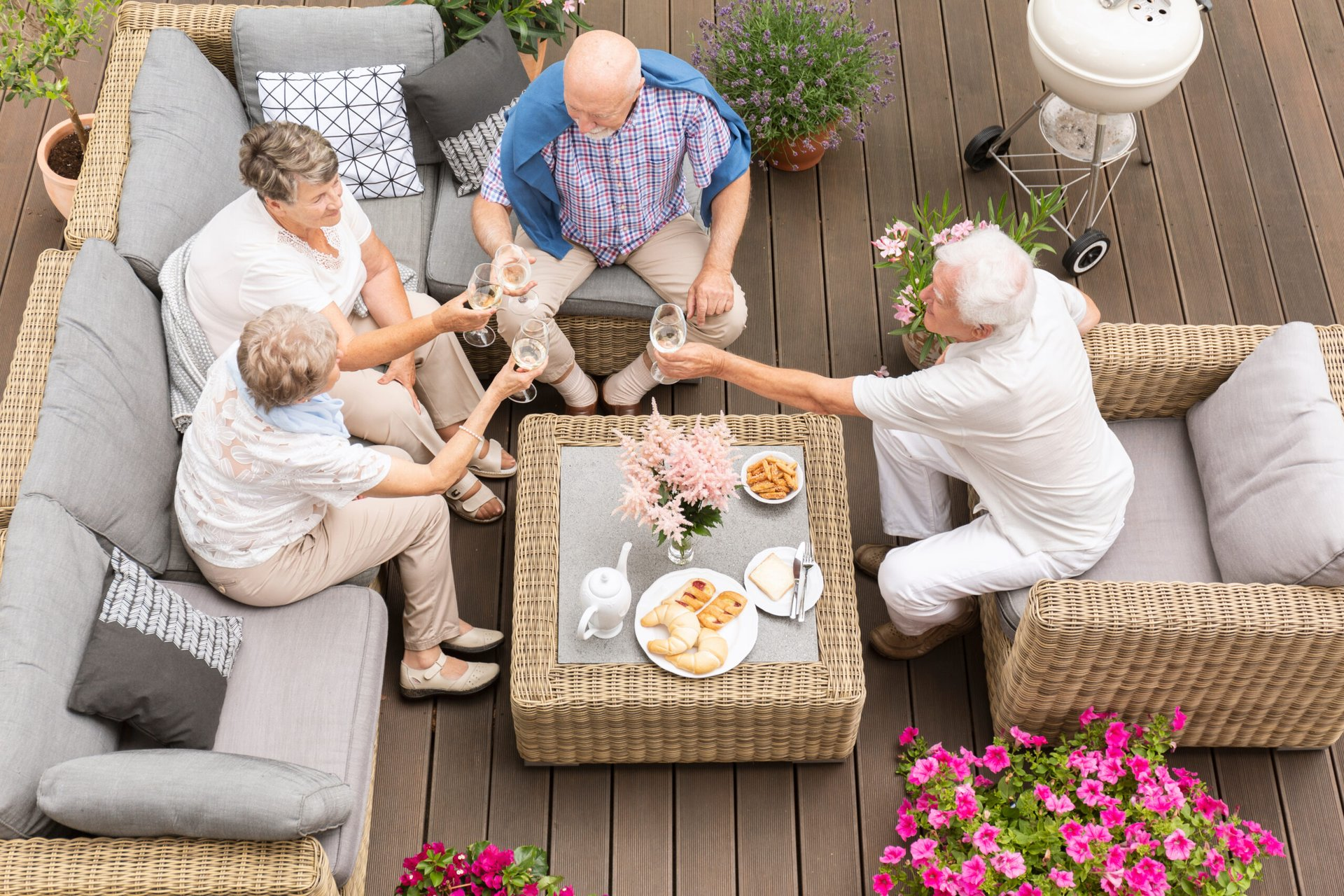 Senior friends eating outdoors on a deck