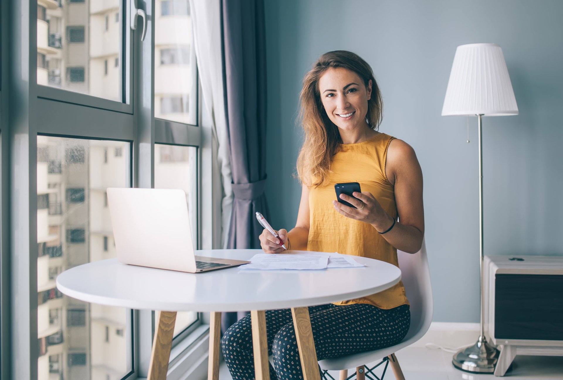 Woman working from home on computer and phone